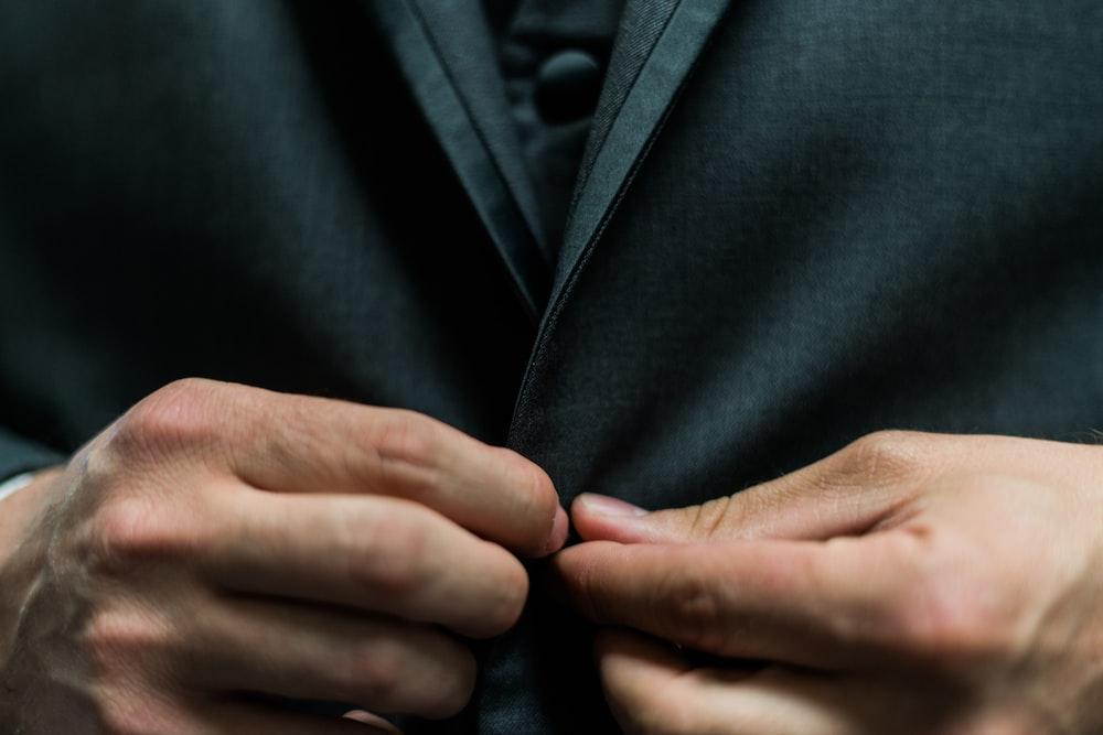 person holding black suit jacket button