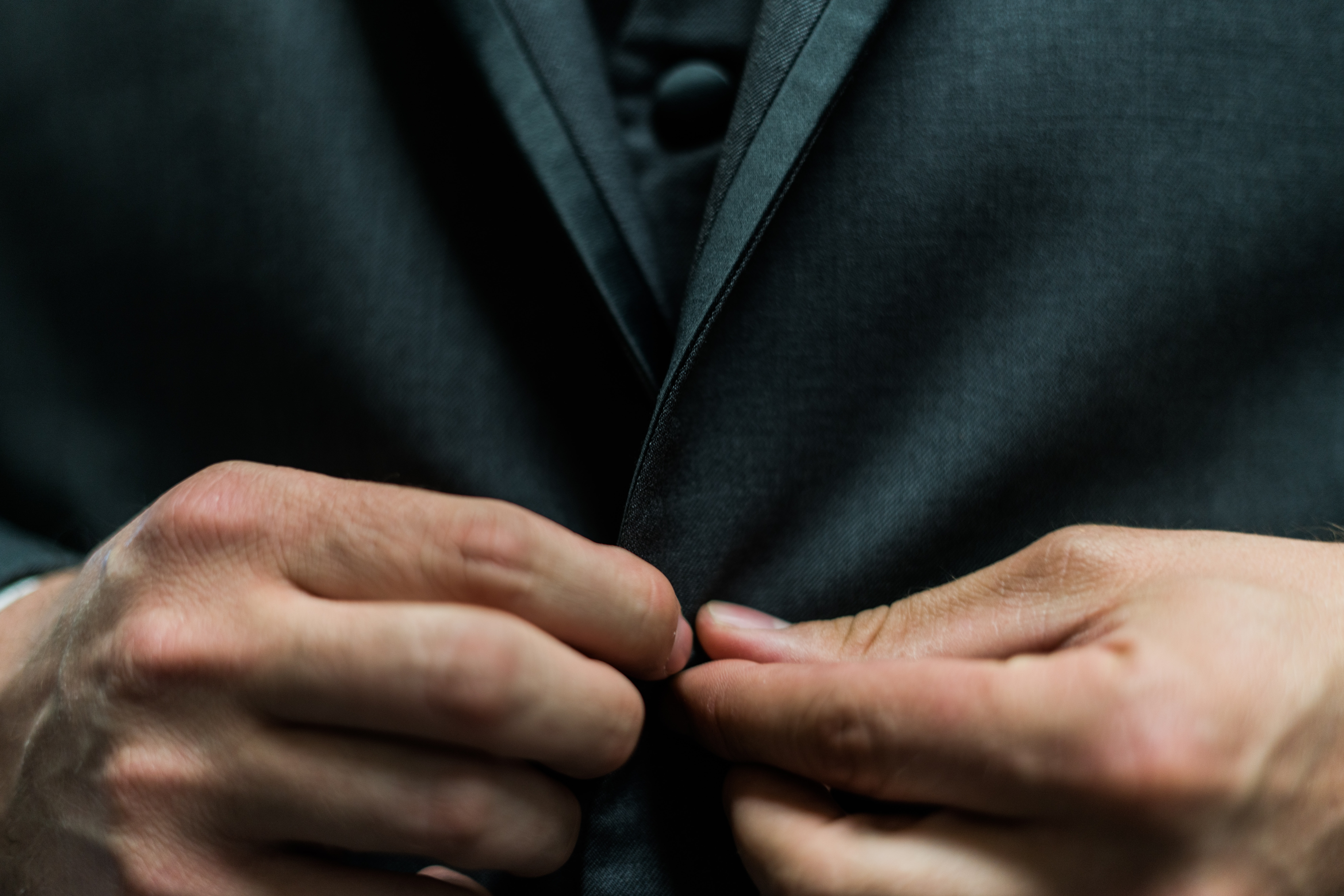 Close-up of a man's hands buttoning his black suit
