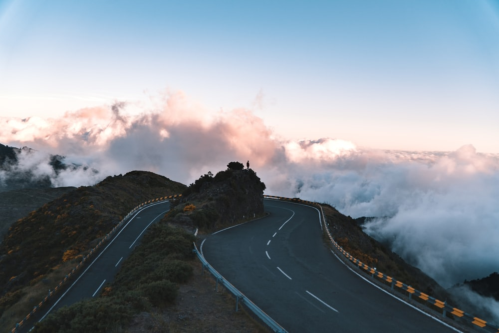 road on hill surrounded with clouds