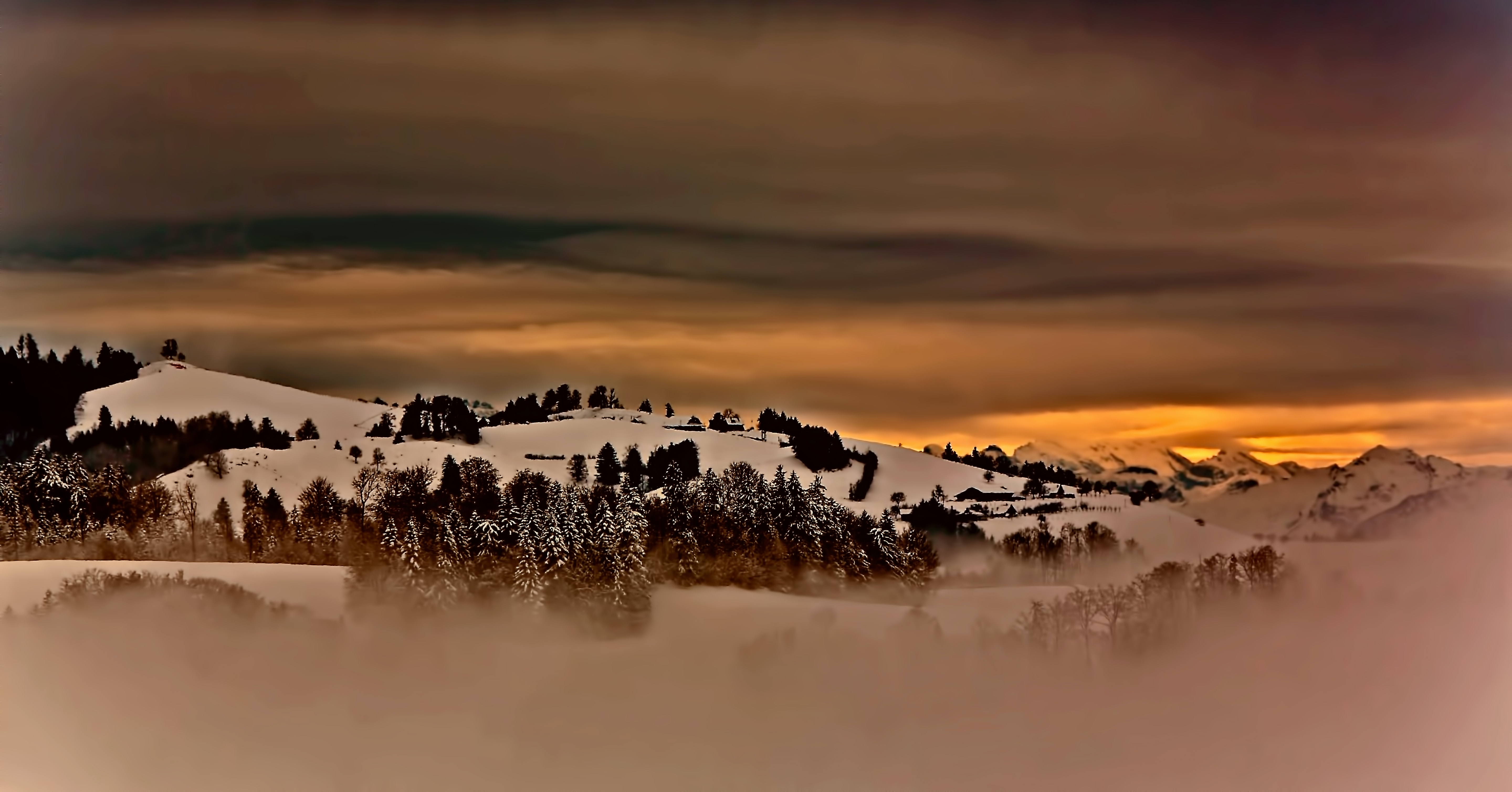 Orange sky shines over a snowy hillscape in Hirzel