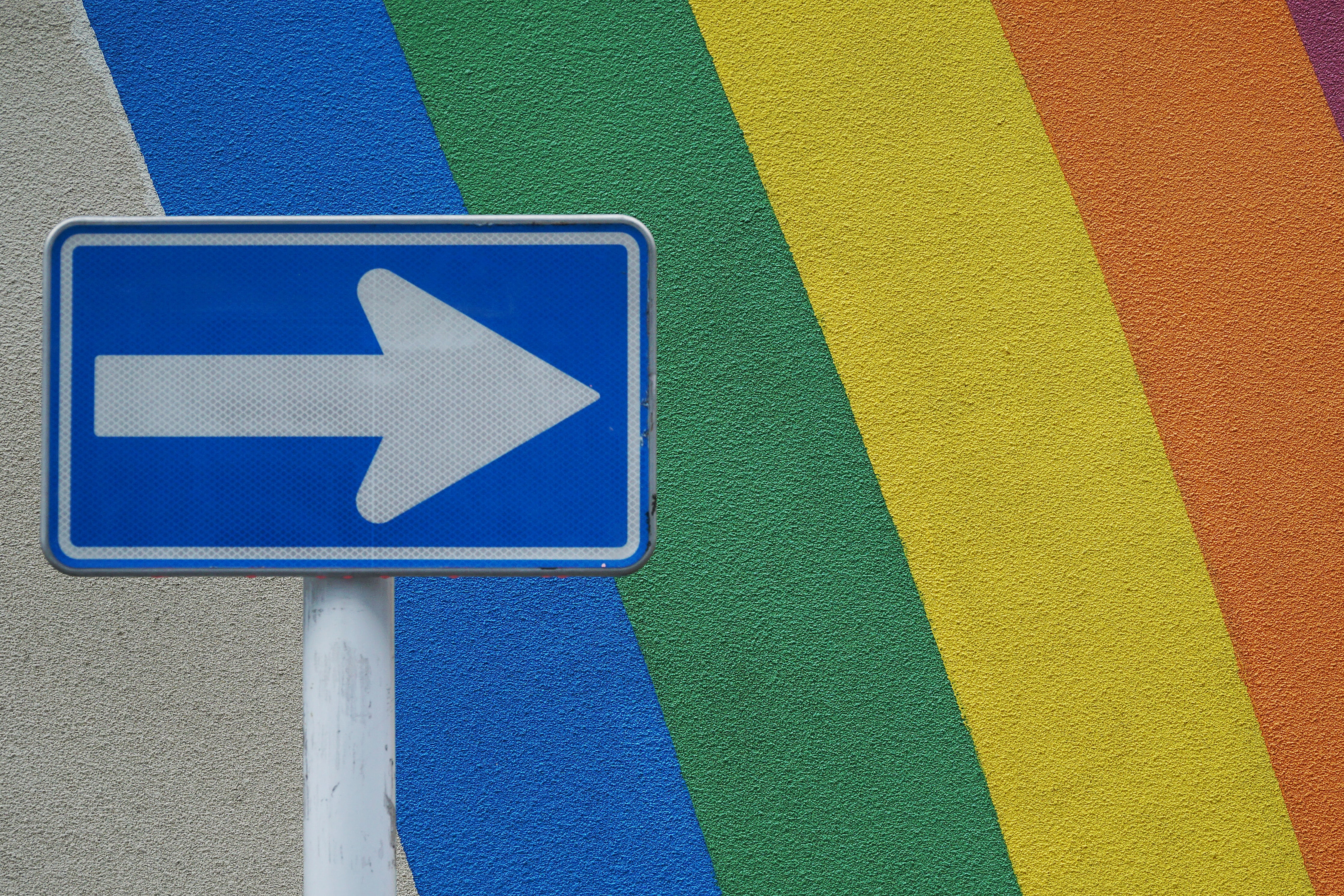 blue and white arrow signage near multicolored wall