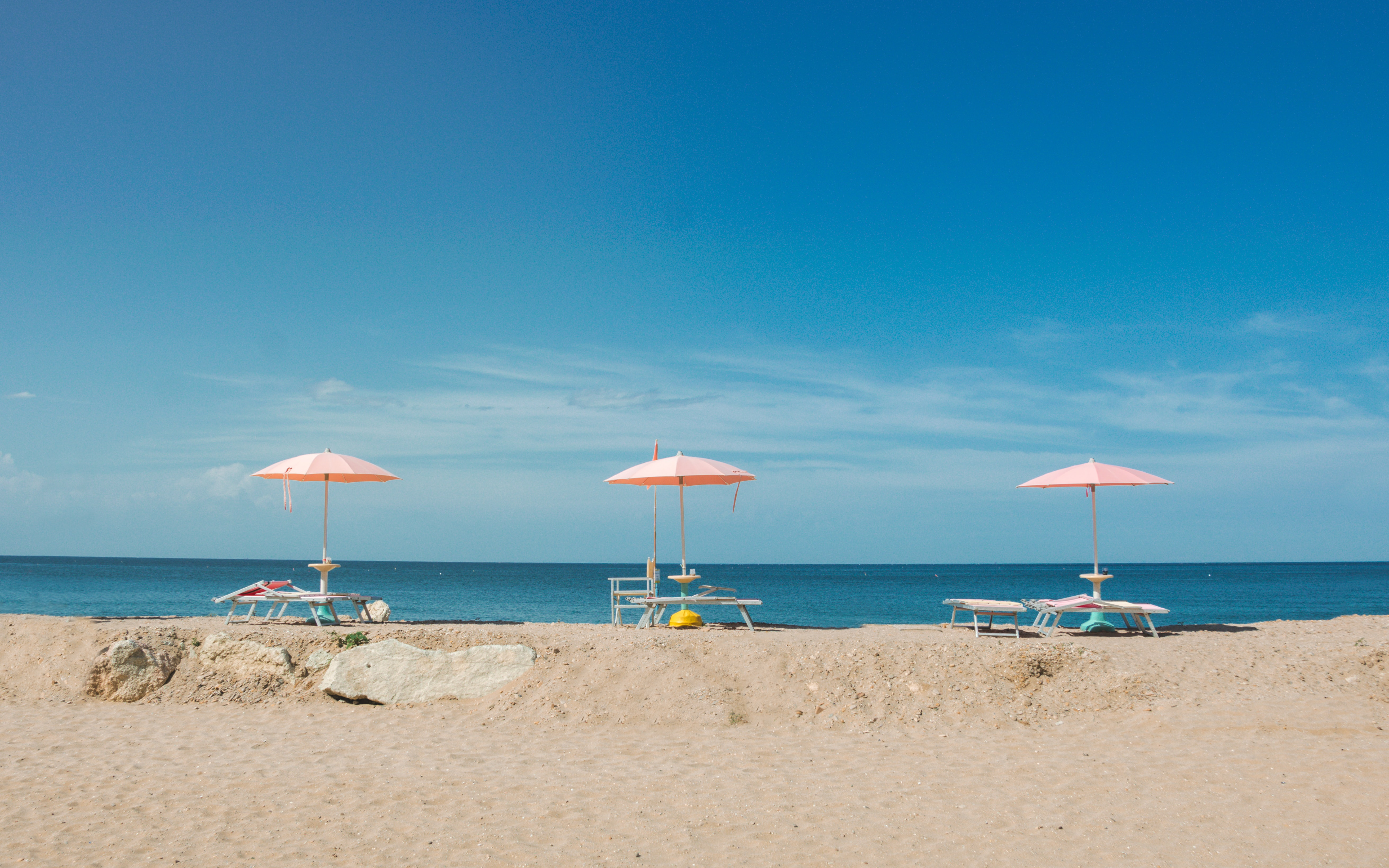 Three pink umbrellas attached to deck chairs on an empty beach