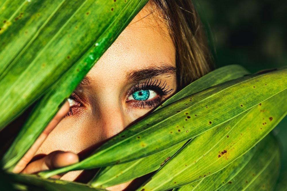 woman behind green leaves