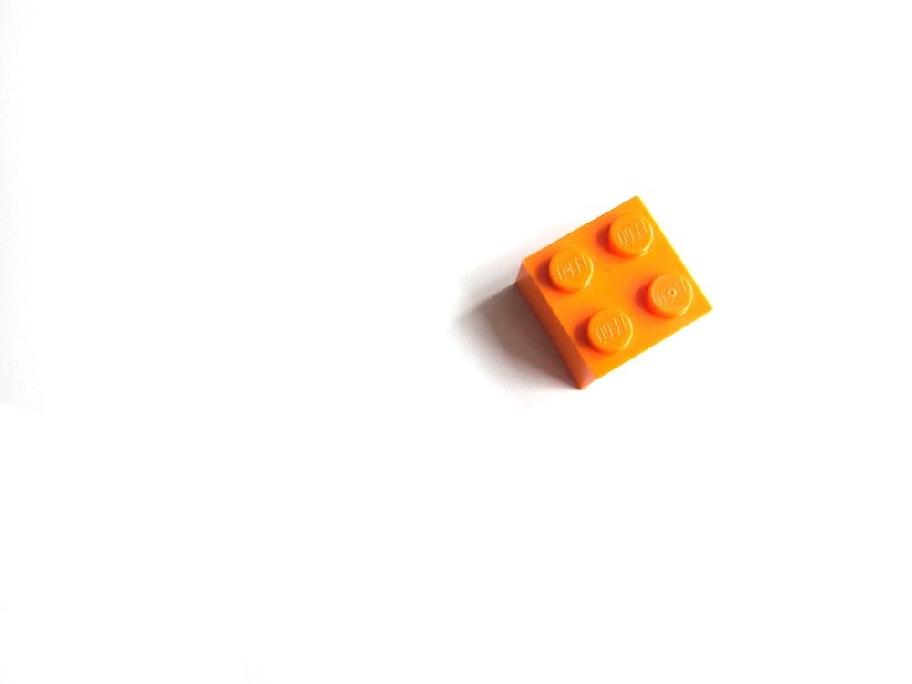 orange mega blocks toy on white surface