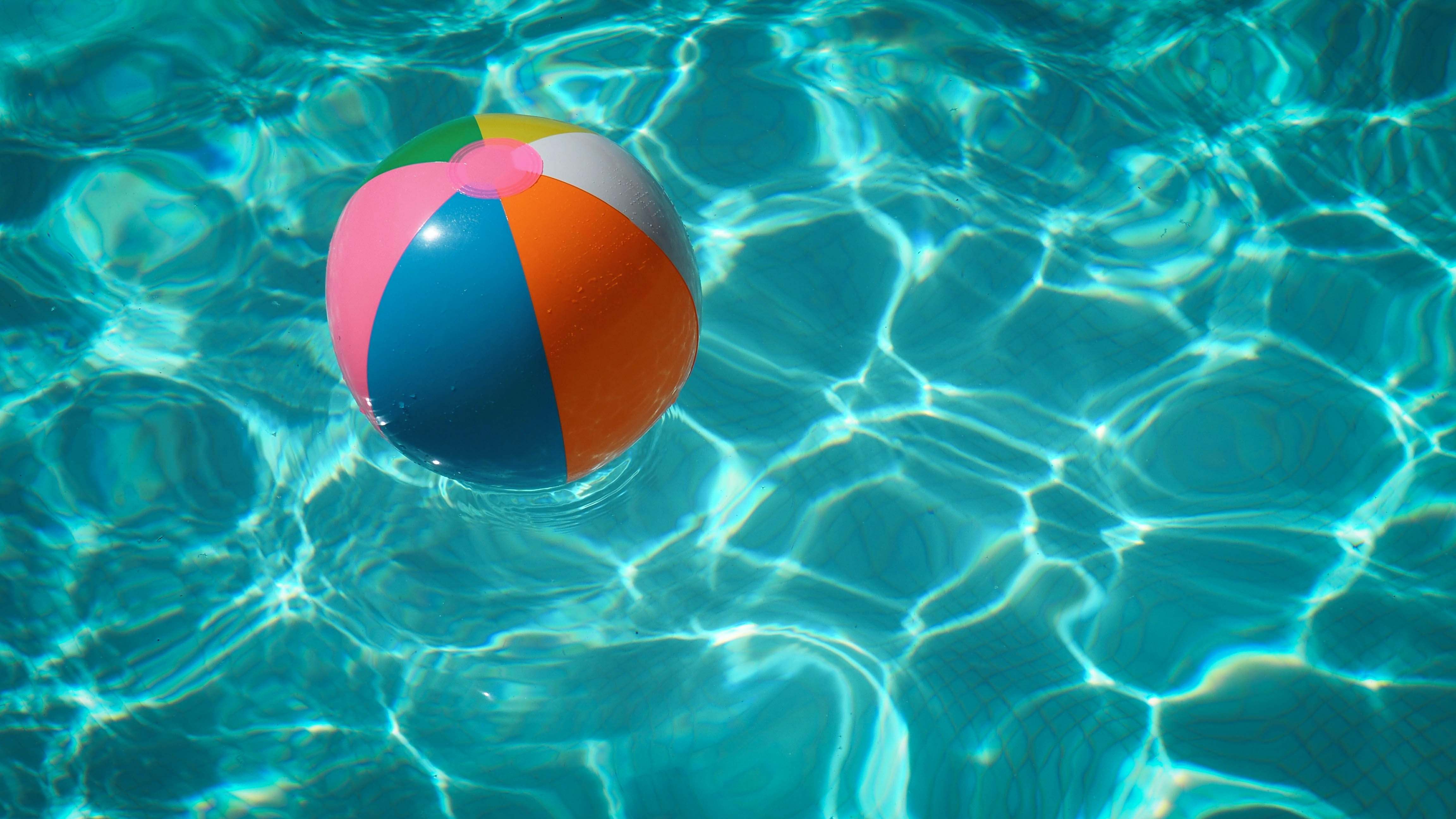 A beach ball floating on water in a swimming pool