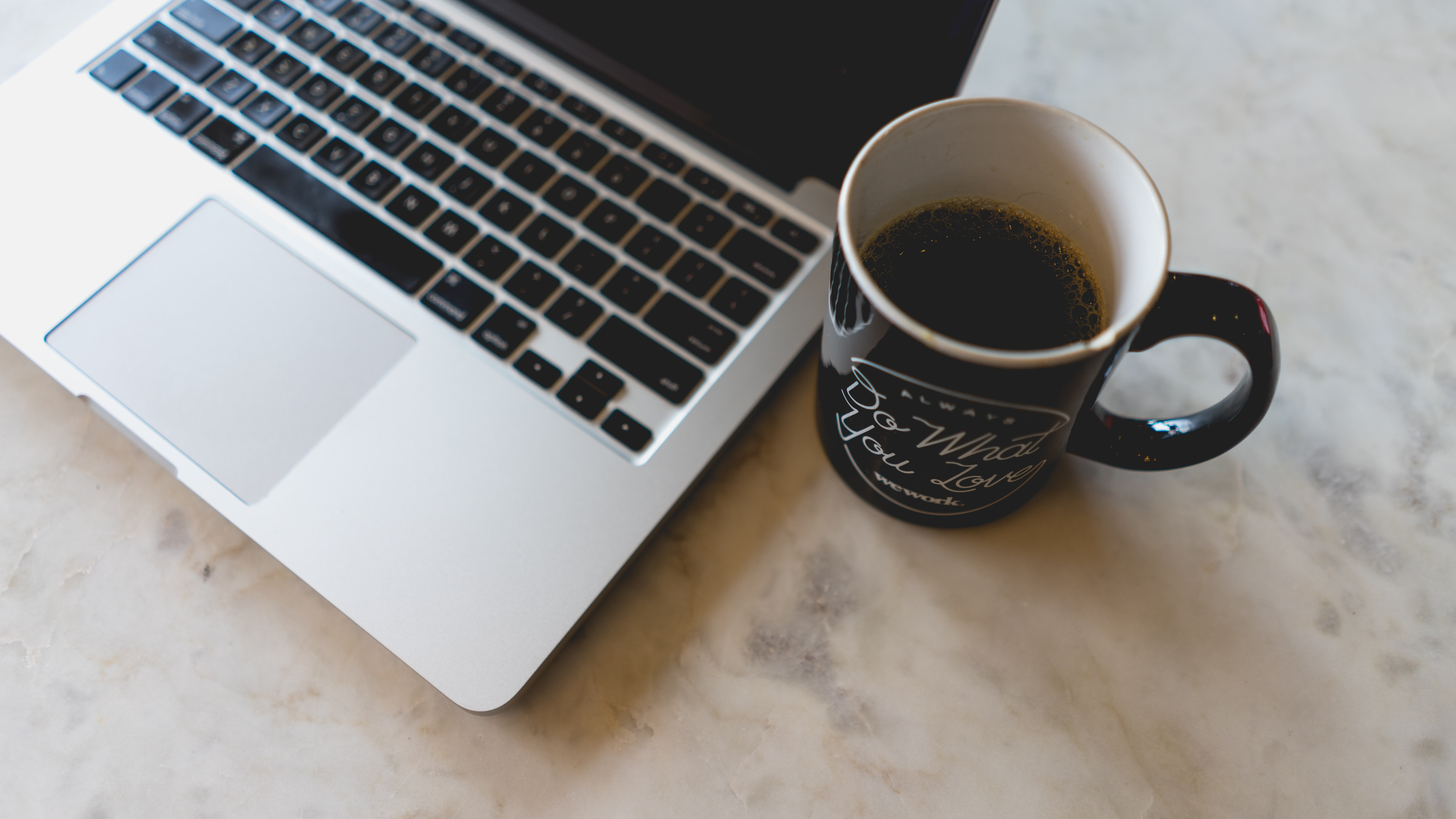A MacBook computer and a cup of coffee