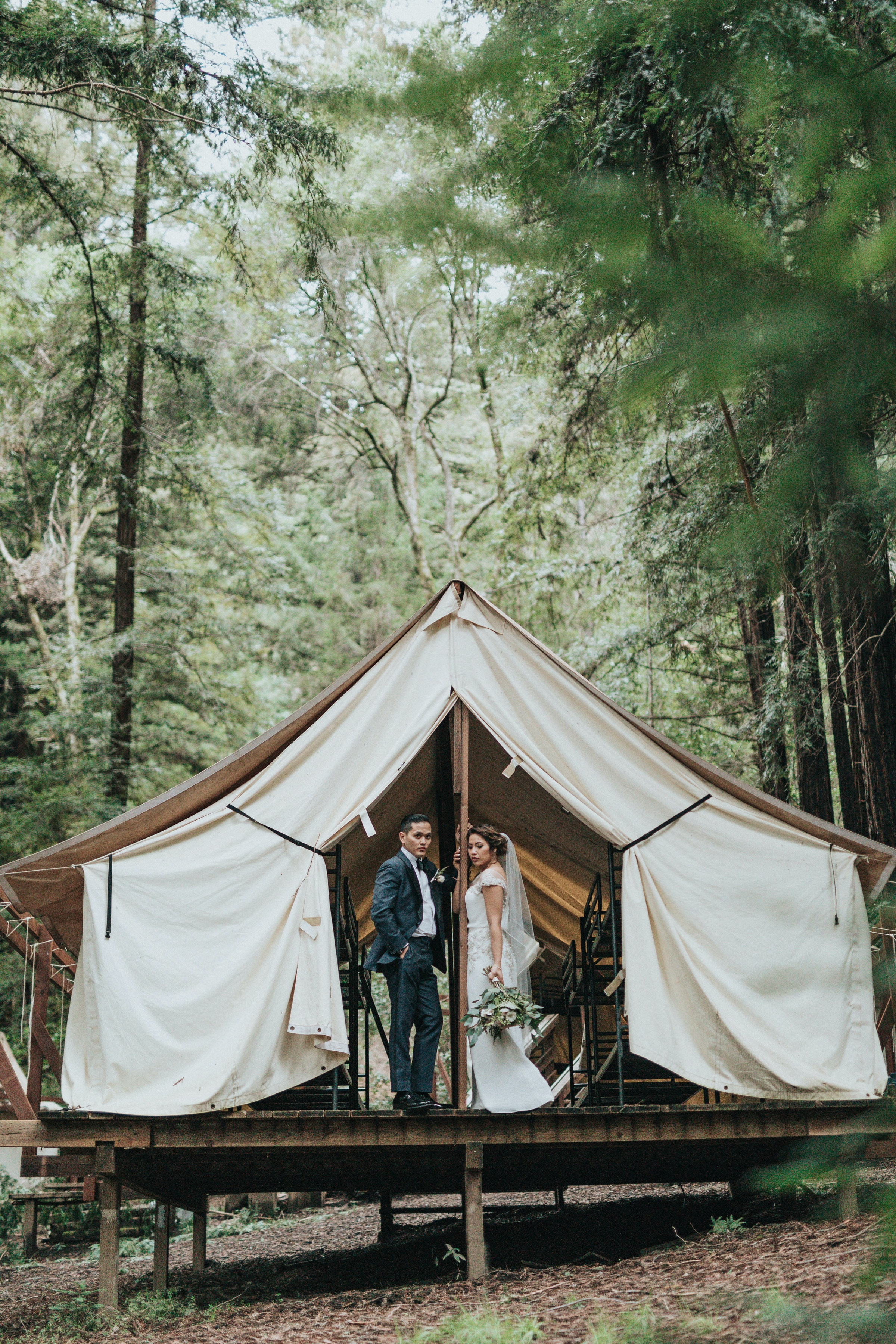 The flaps of a tent in the woods are opened to reveal a married couple in wedding wear