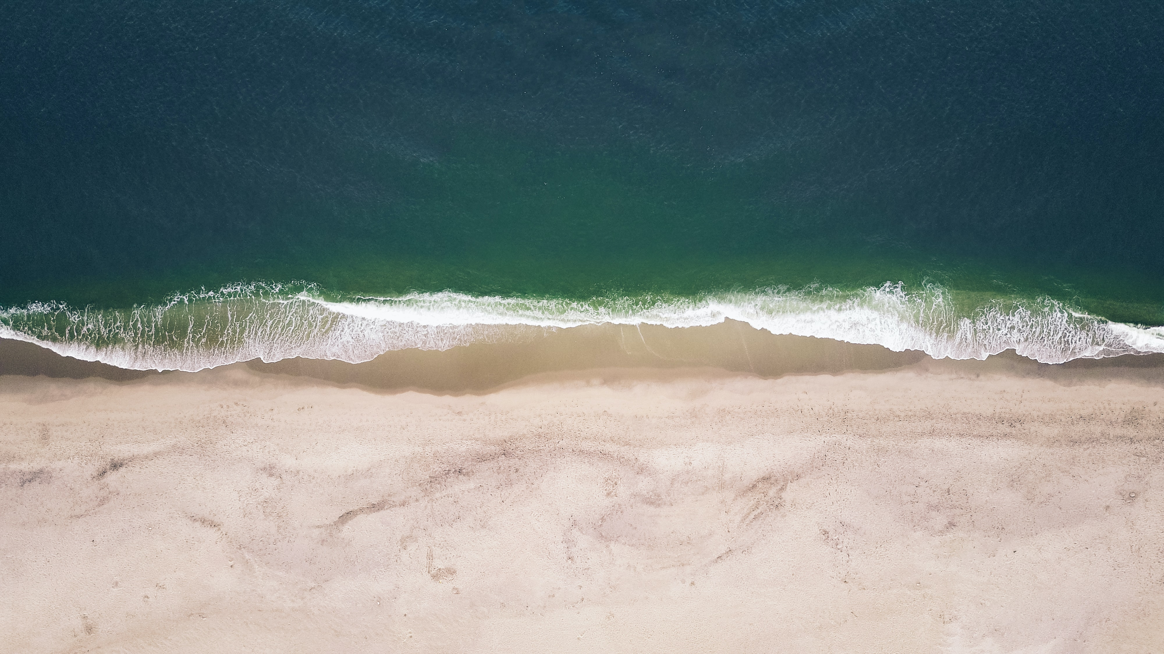 An aerial view of waves crashing on an empty beach