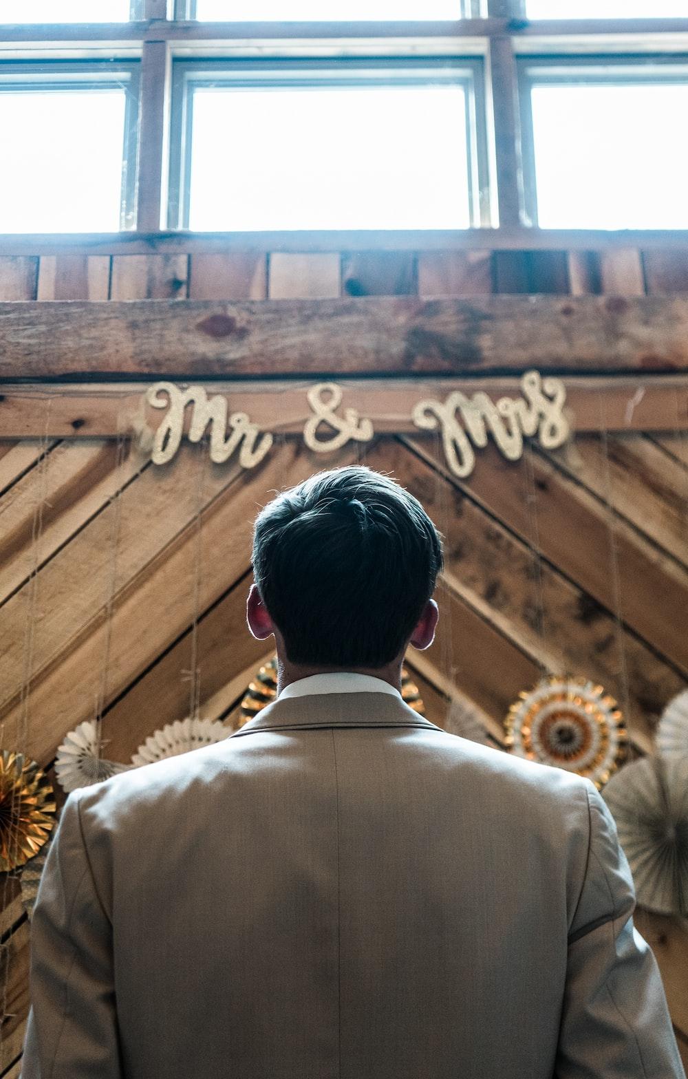 man in beige suit jacket standing in front of brown wooden wall