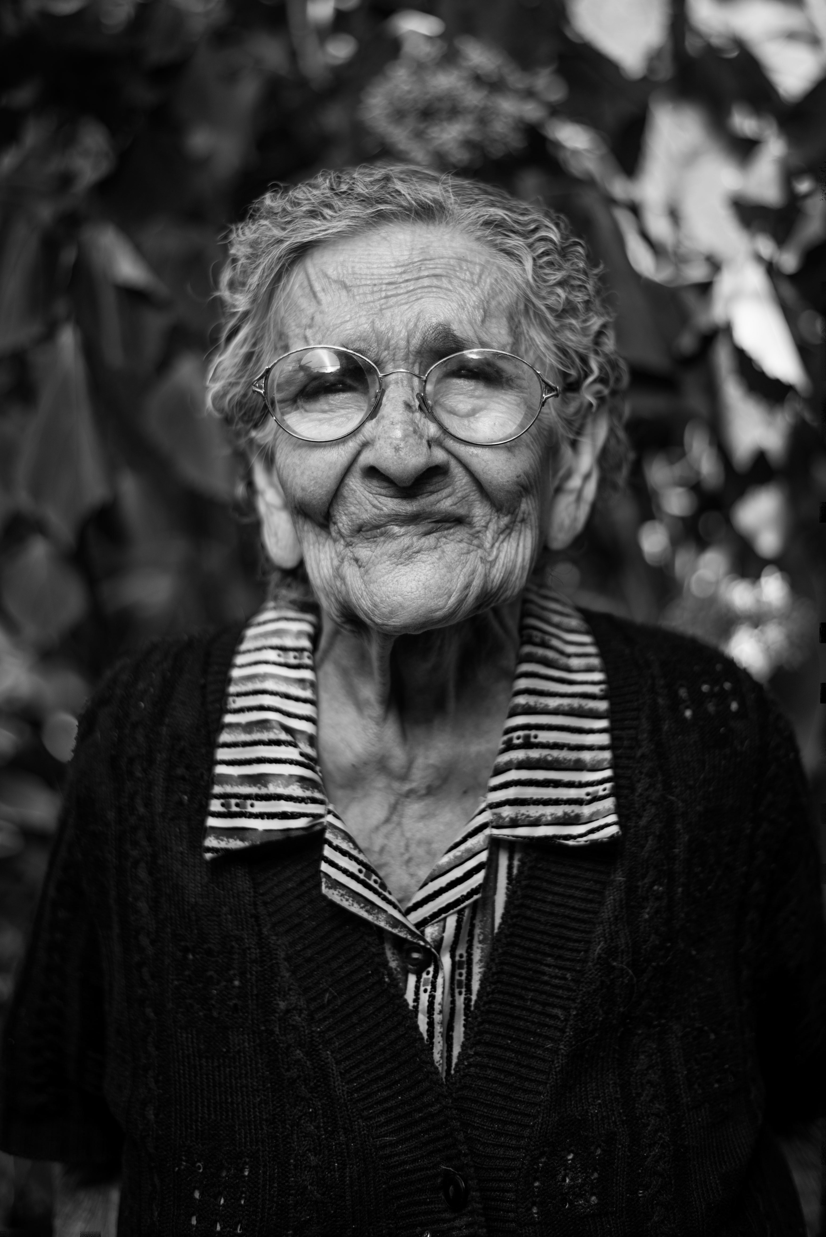 An old retired women with circular glasses in a black and white close-up macro portrait.