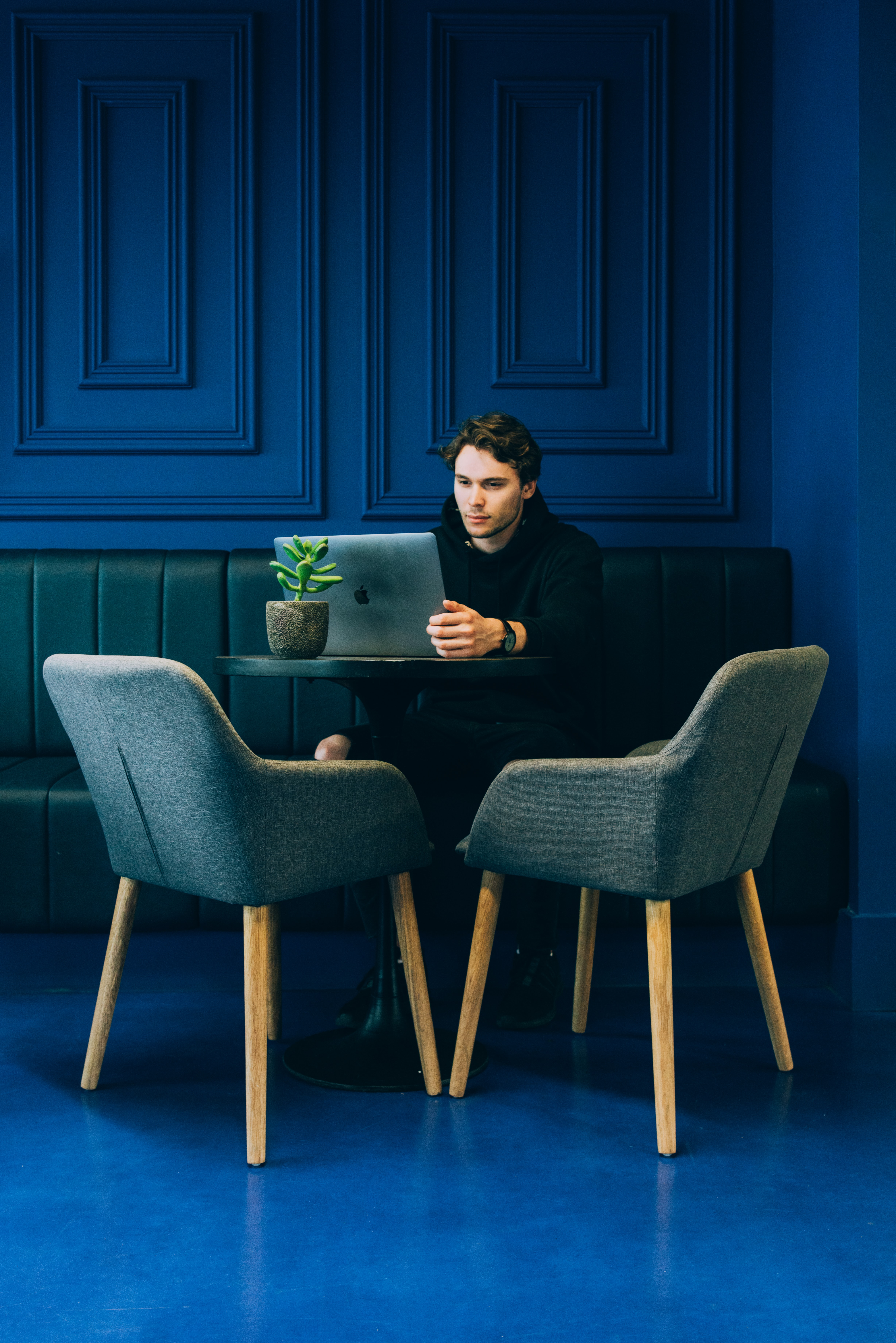 A man looking at a laptop on a leather seat at a blue wall