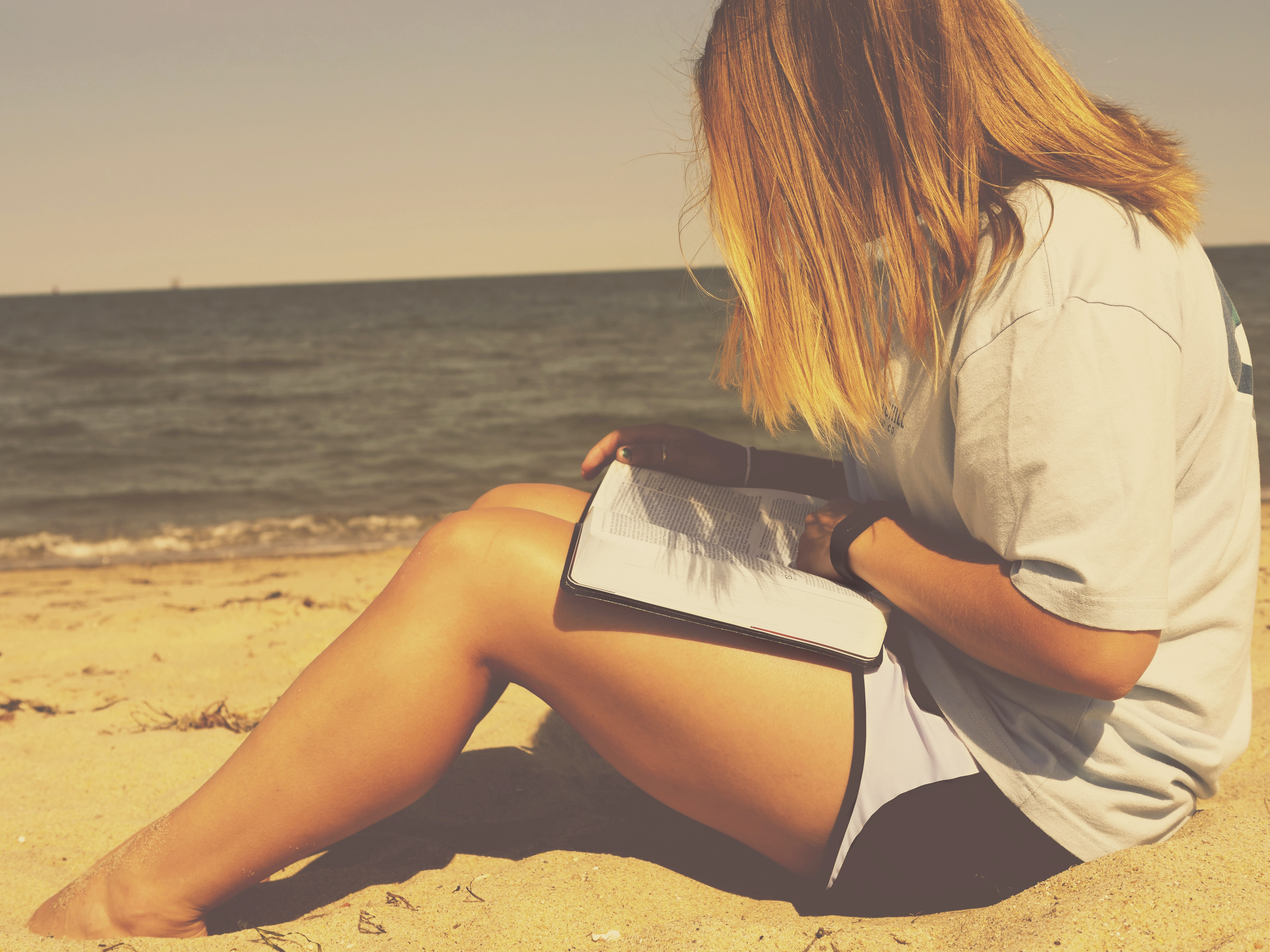 A blonde woman sitting on the beach looking at her book.