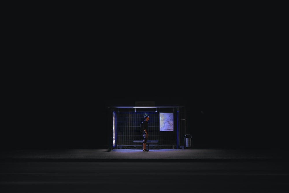 man waiting on shed during nightime