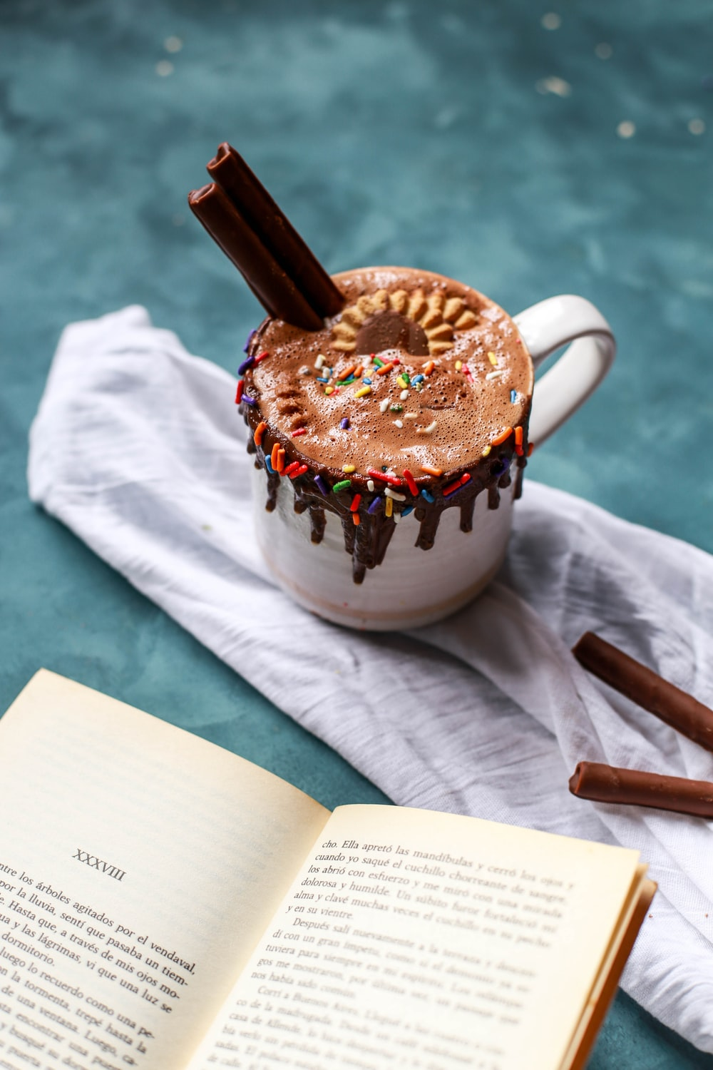 closeup photo of white mug full of chocolate drink with sprinkles and cookies