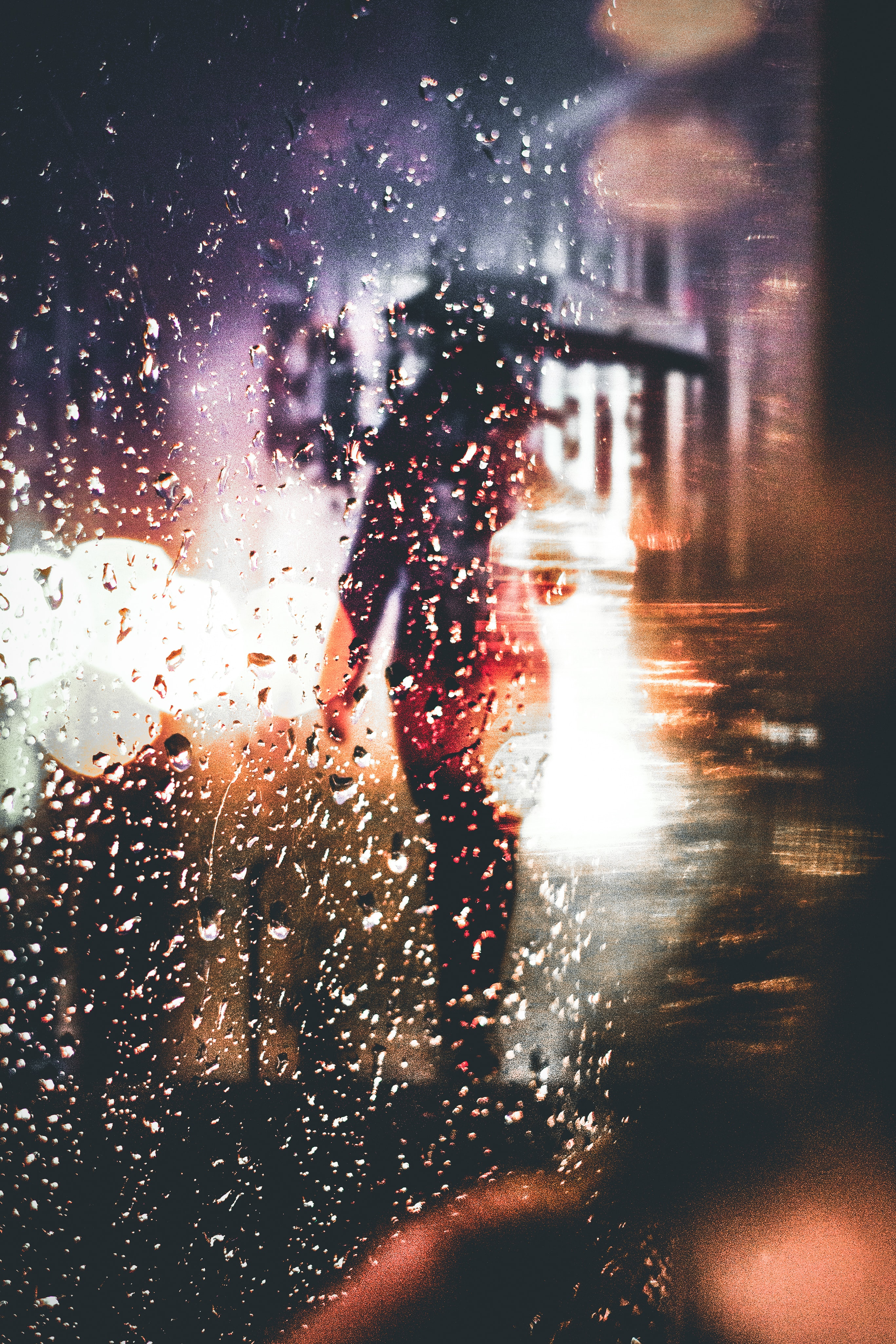 Silhouette of a person with an umbrella walking in the rain during night-time in Melbourne