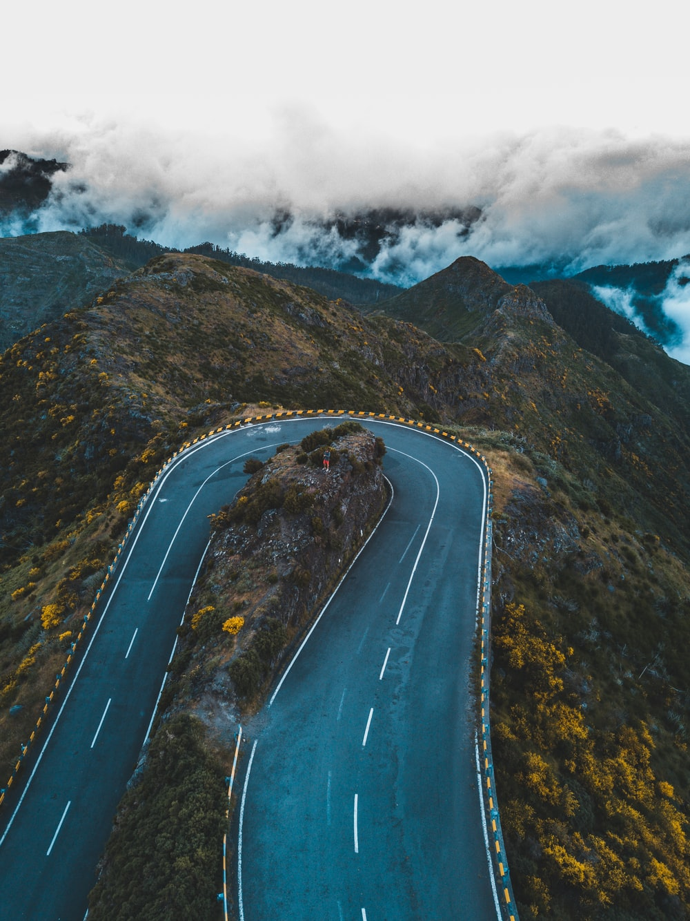 aerial photography of mountain pass under white clouds