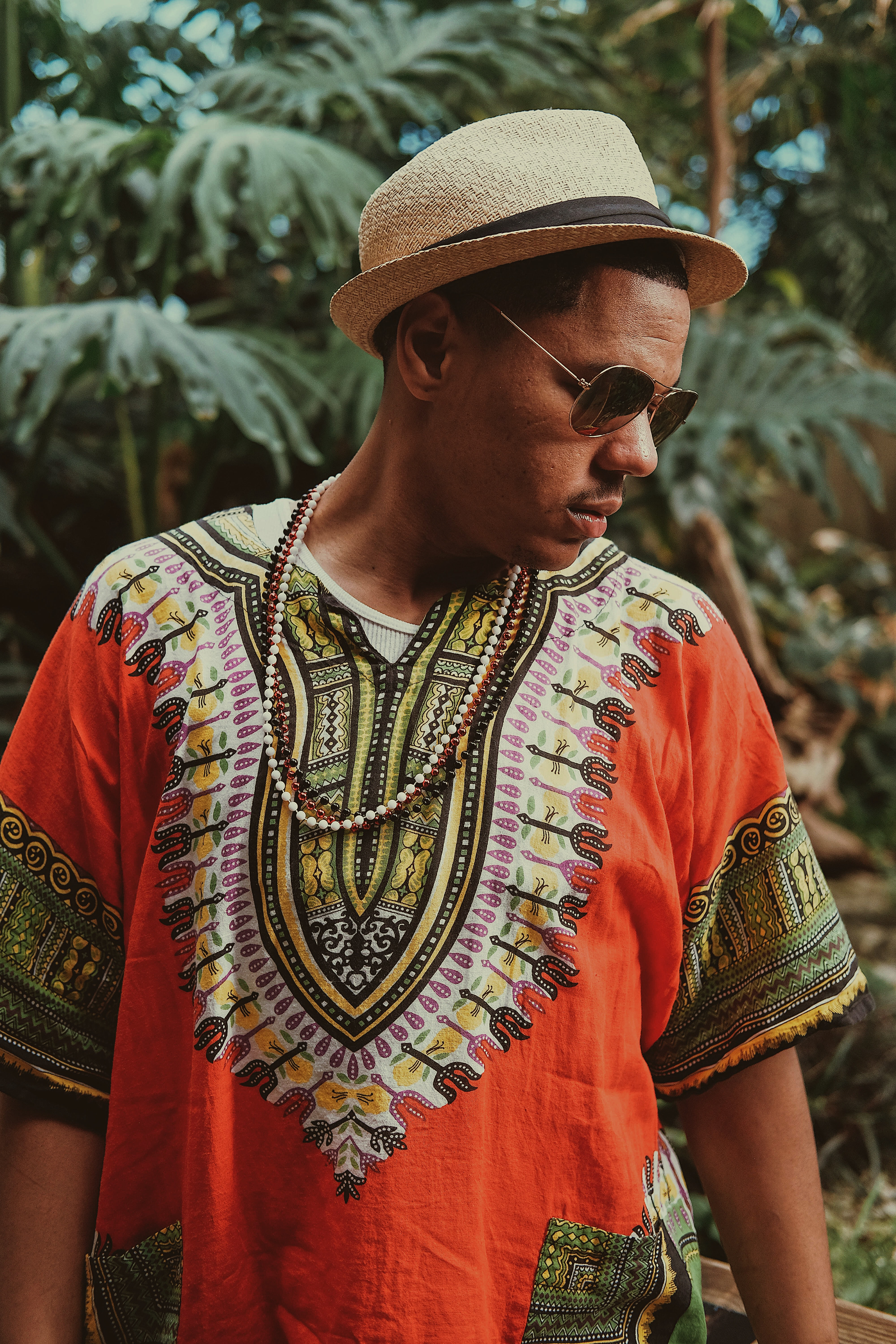 A man in a colorful dashiki, sunglasses, and straw hat looks to the side in Tulsa