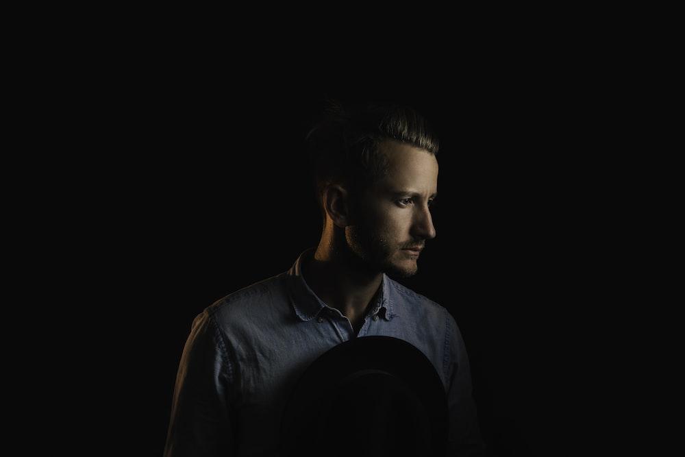 man wearing blue button-up shirt on black background
