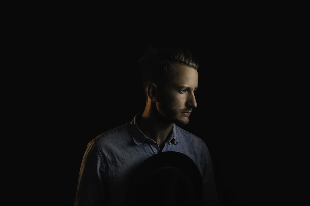 man wearing blue button-up shirt on black background