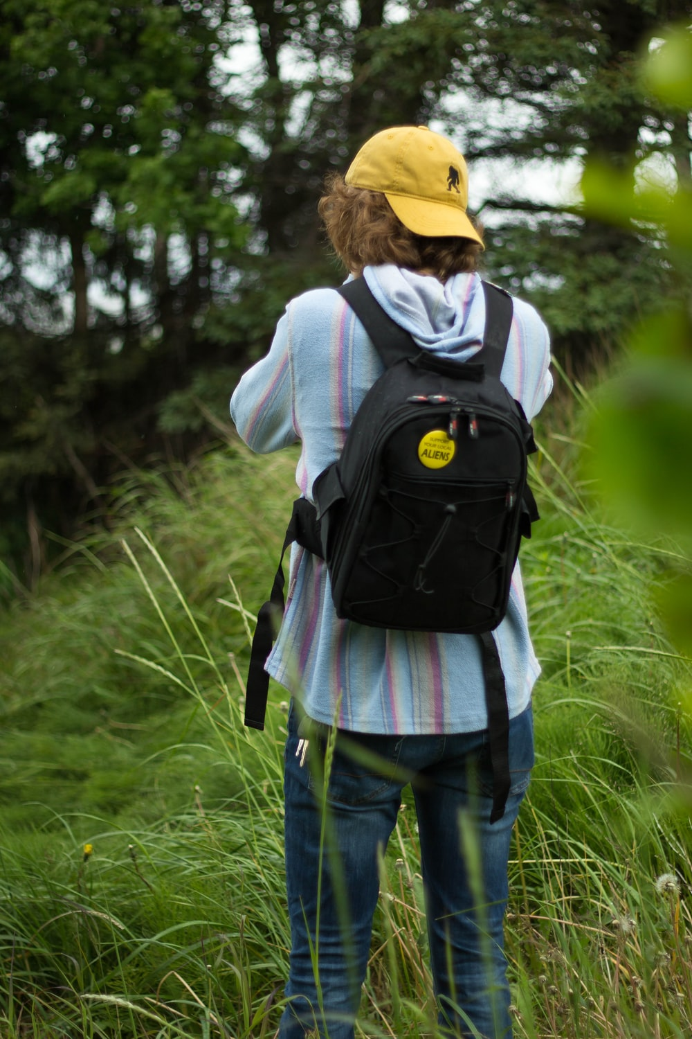 woman in gray hoodie and blue denim jeans with black backpack walking on green grass field
