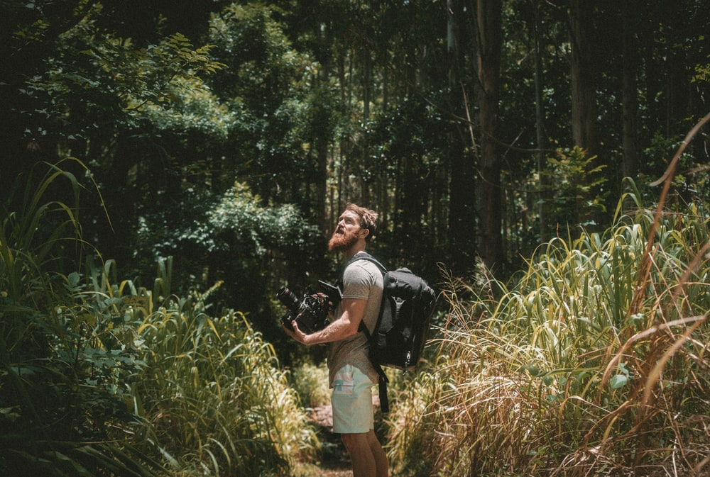 man holding camera in the forest