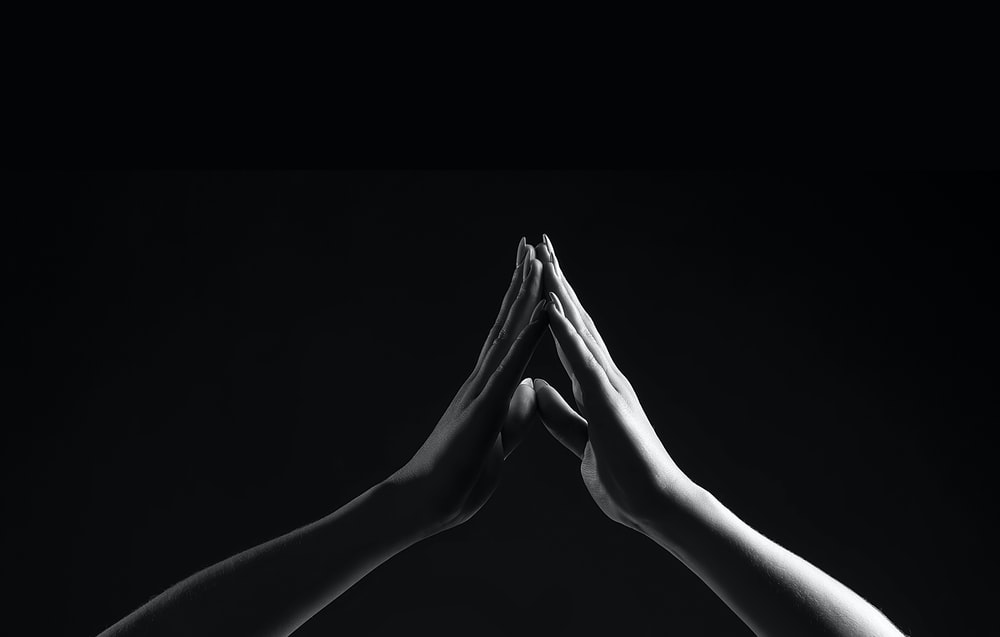 person's hands forming triangle