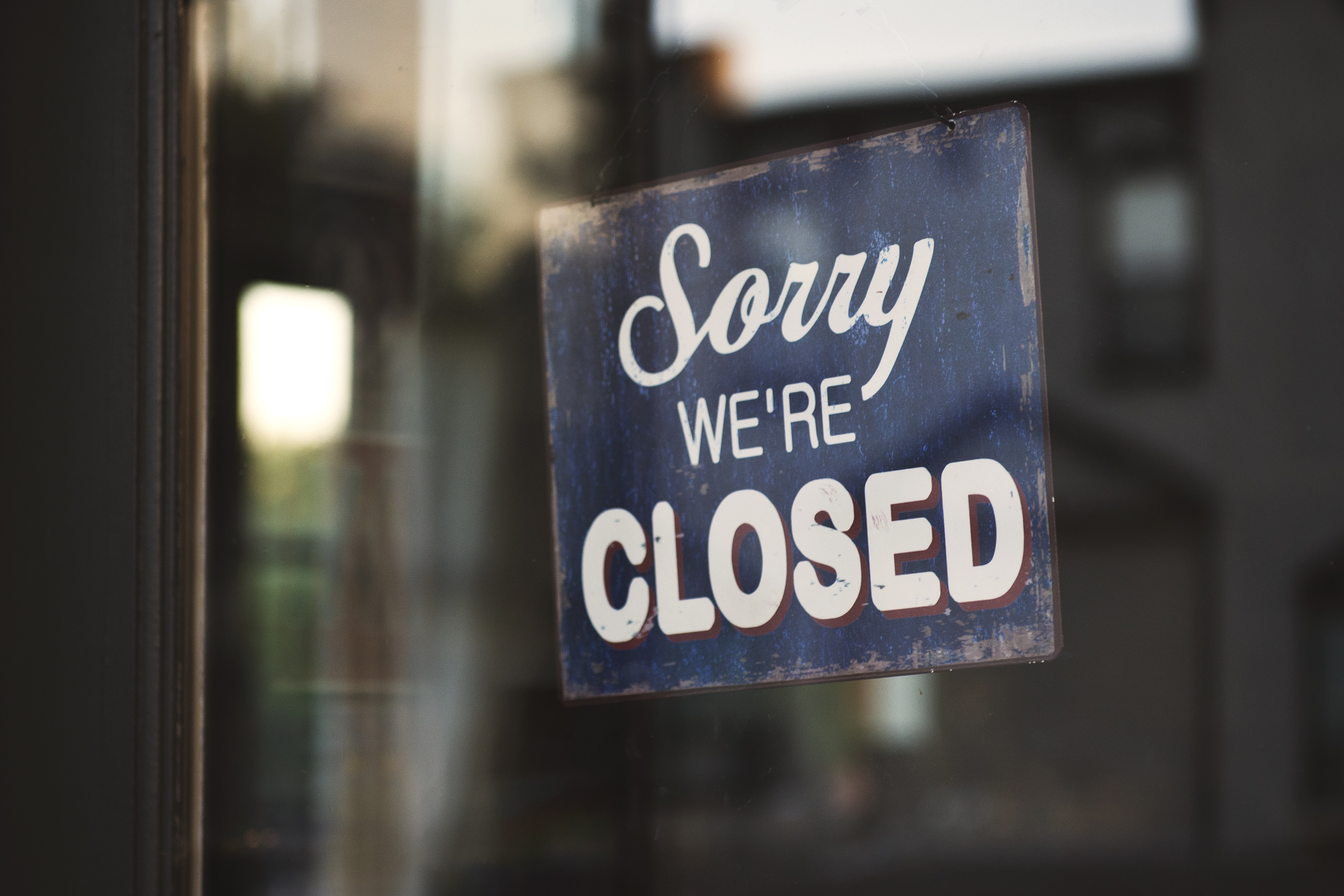 """A """"Sorry, we're closed"""" sign hanging in a store window"""