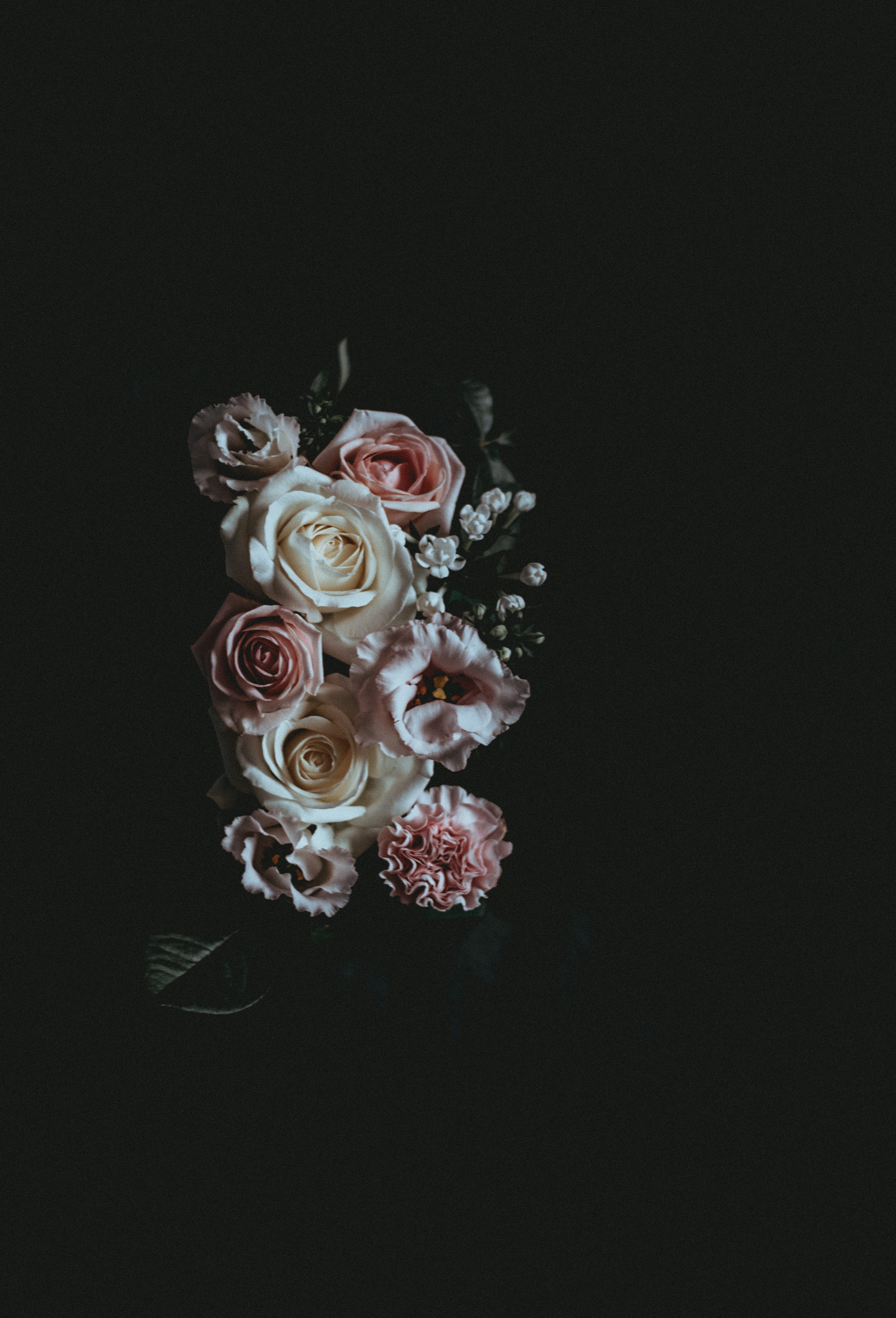 A dark photo of a flower arrangement consisting of pink and white roses