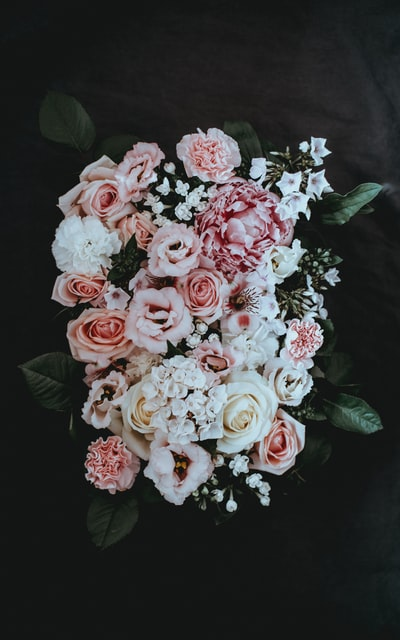 Pale pinks and whites arranged in a florists oasis, sat on top of a (very unglamorous) dark grey tshirt.  Part of a series of dark florals, you can find the rest on my Unsplash profile ❤️