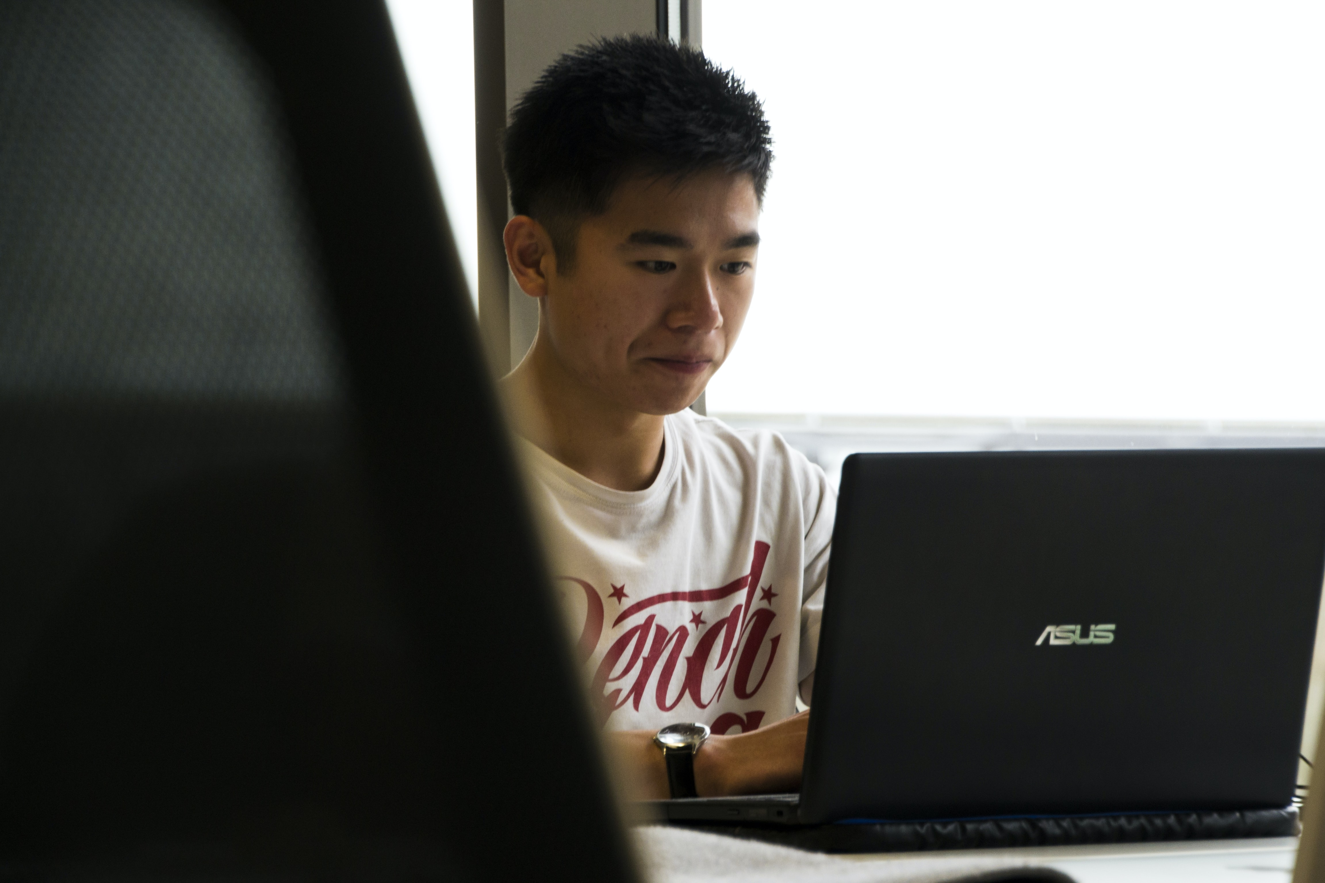 A young man sitting at a black laptop
