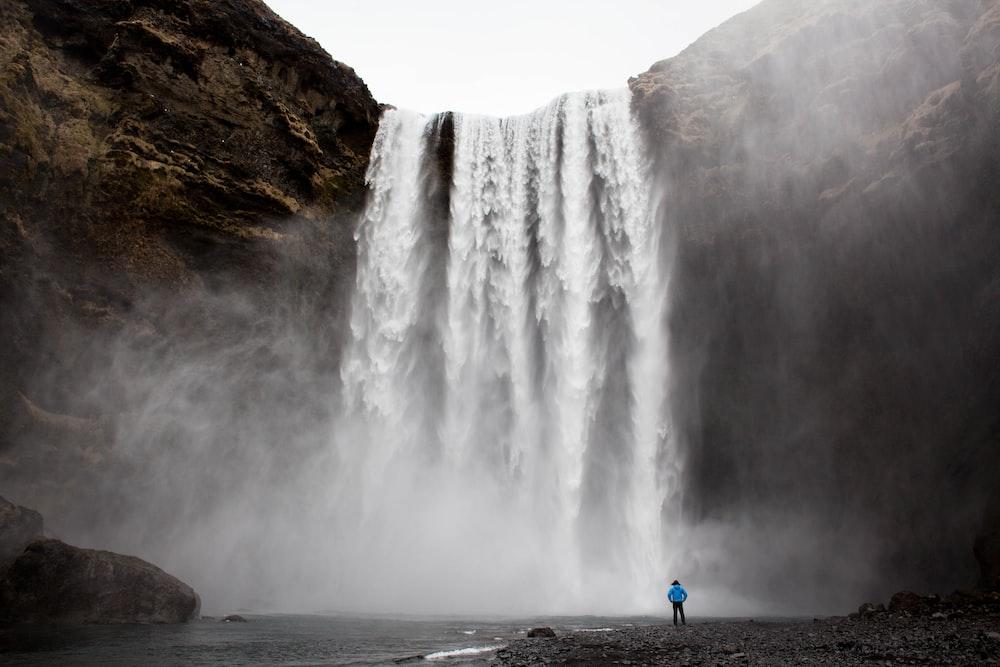 man standing front of waterfalls at daytime