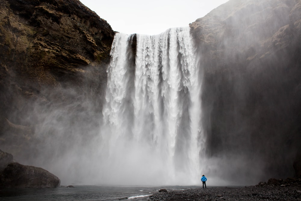 man standing front of waterfalls at daytime