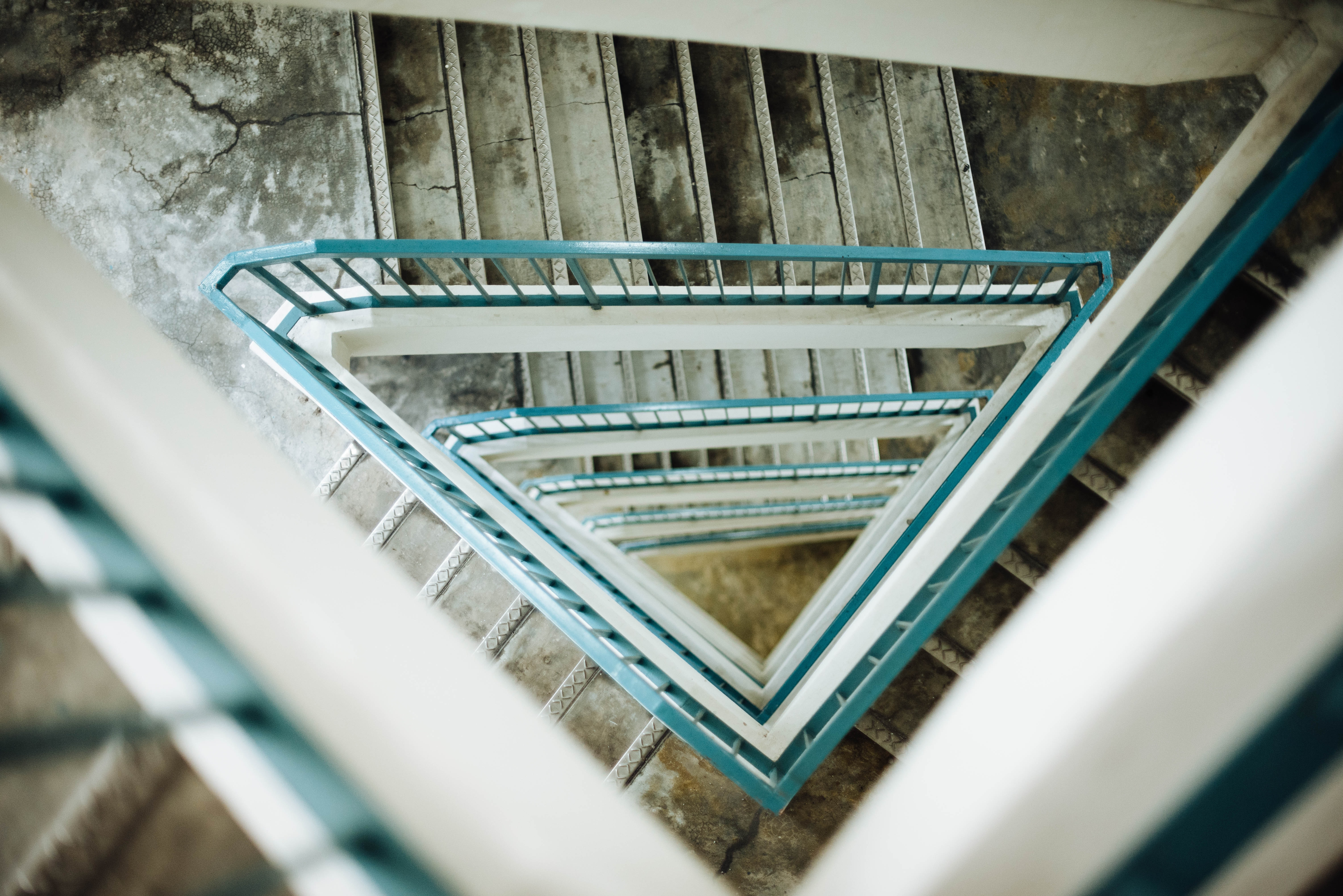 Looking down at the view of a triangular stairwell with teal-coloured handrails and slightly damaged steps