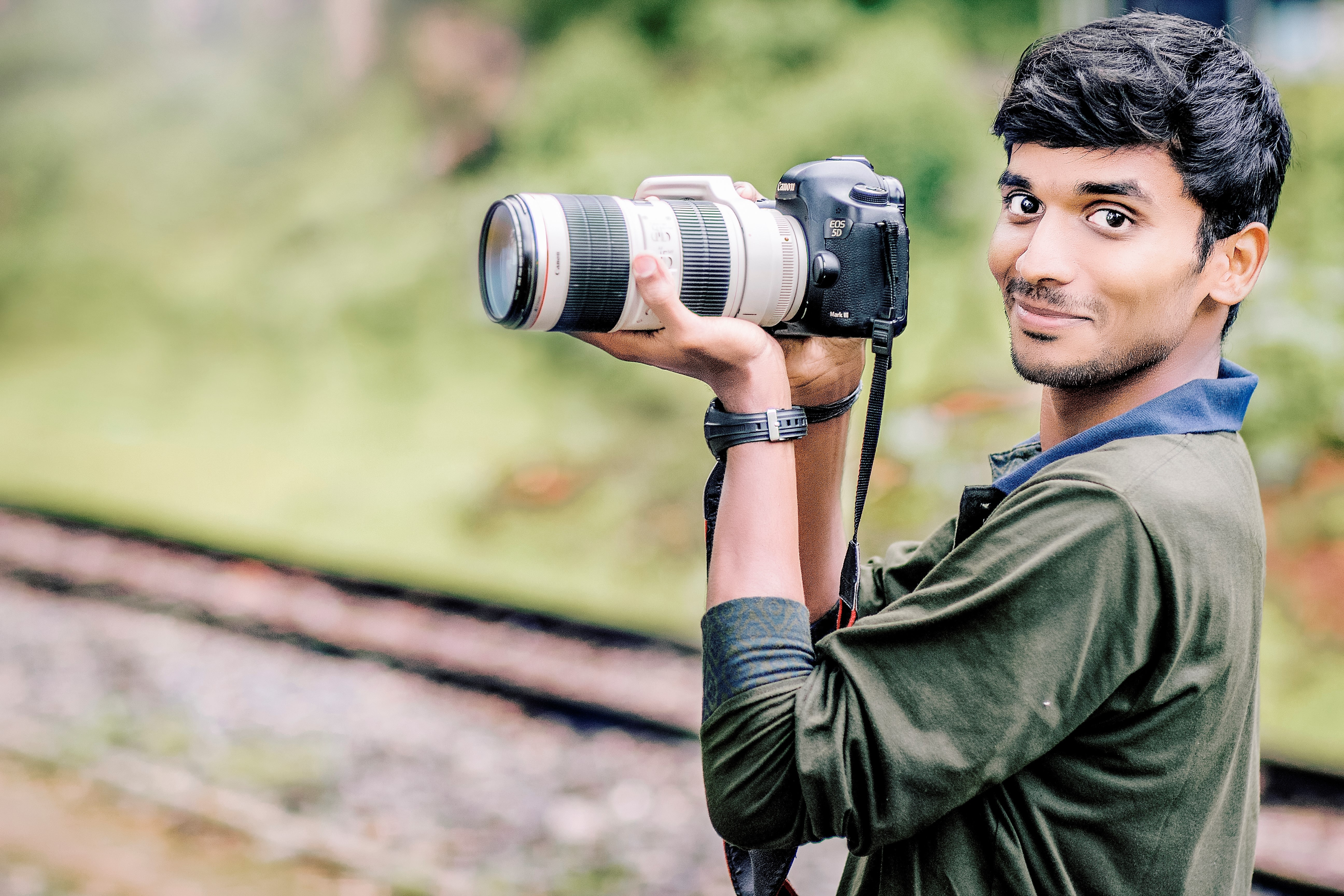 A man holding a Canon camera with a large telephoto lens on it in Ooty