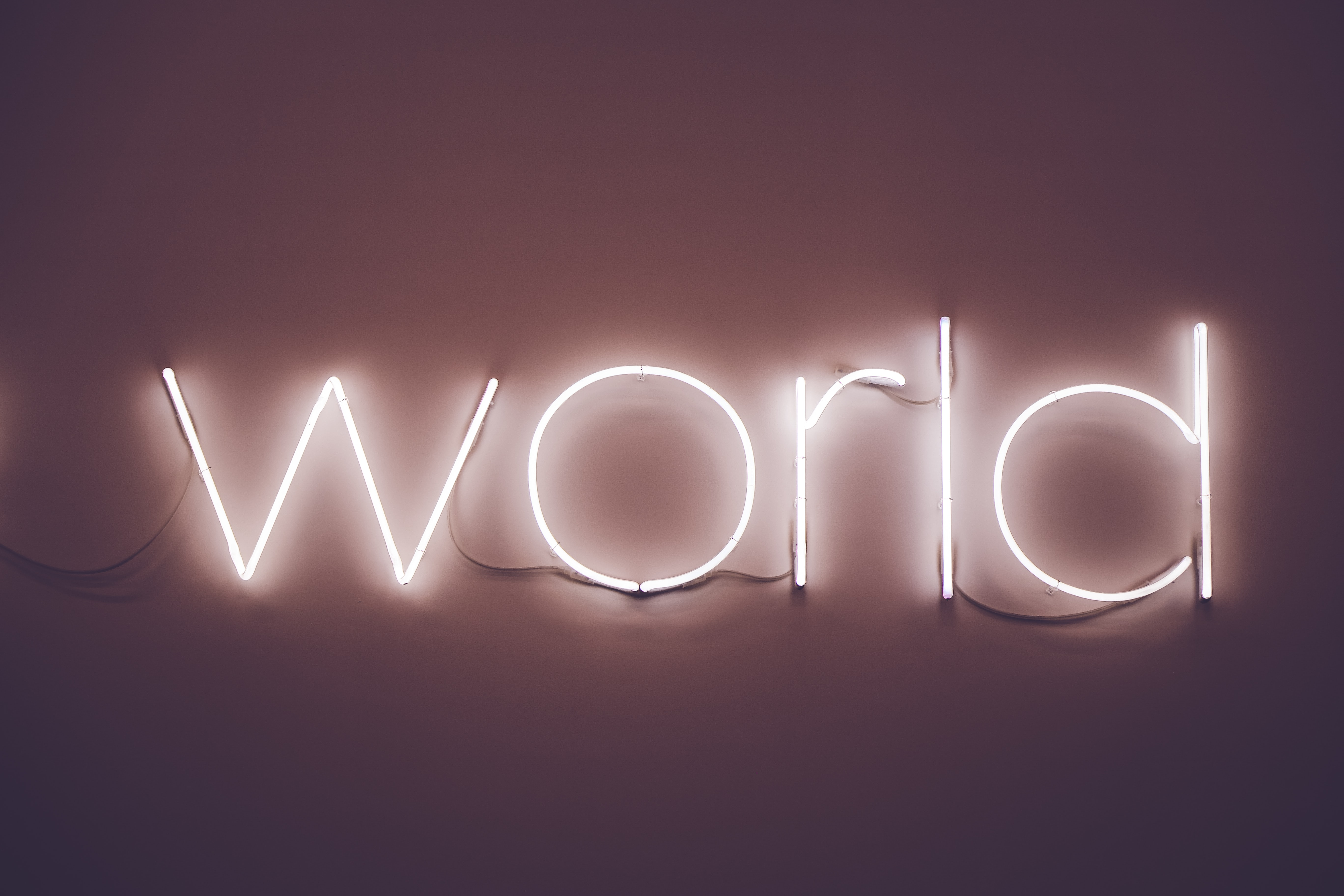 """A white neon on a wall reads """"world"""""""