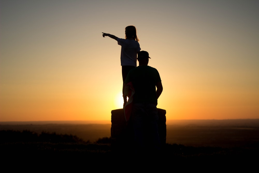 silhouette photo of two person sitting on cliff