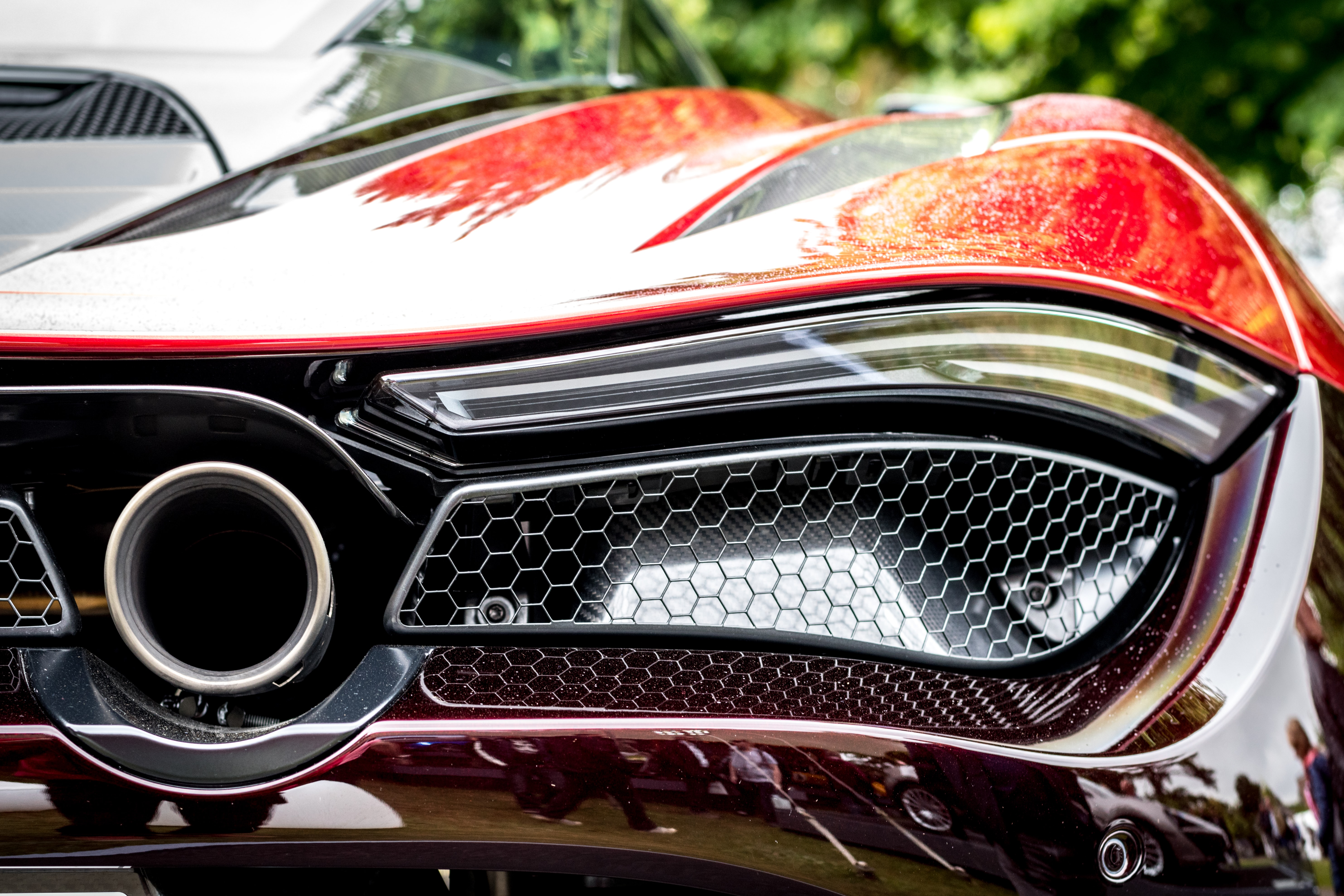 Macro view of a sports car's chrome grille and exhaust pipe.