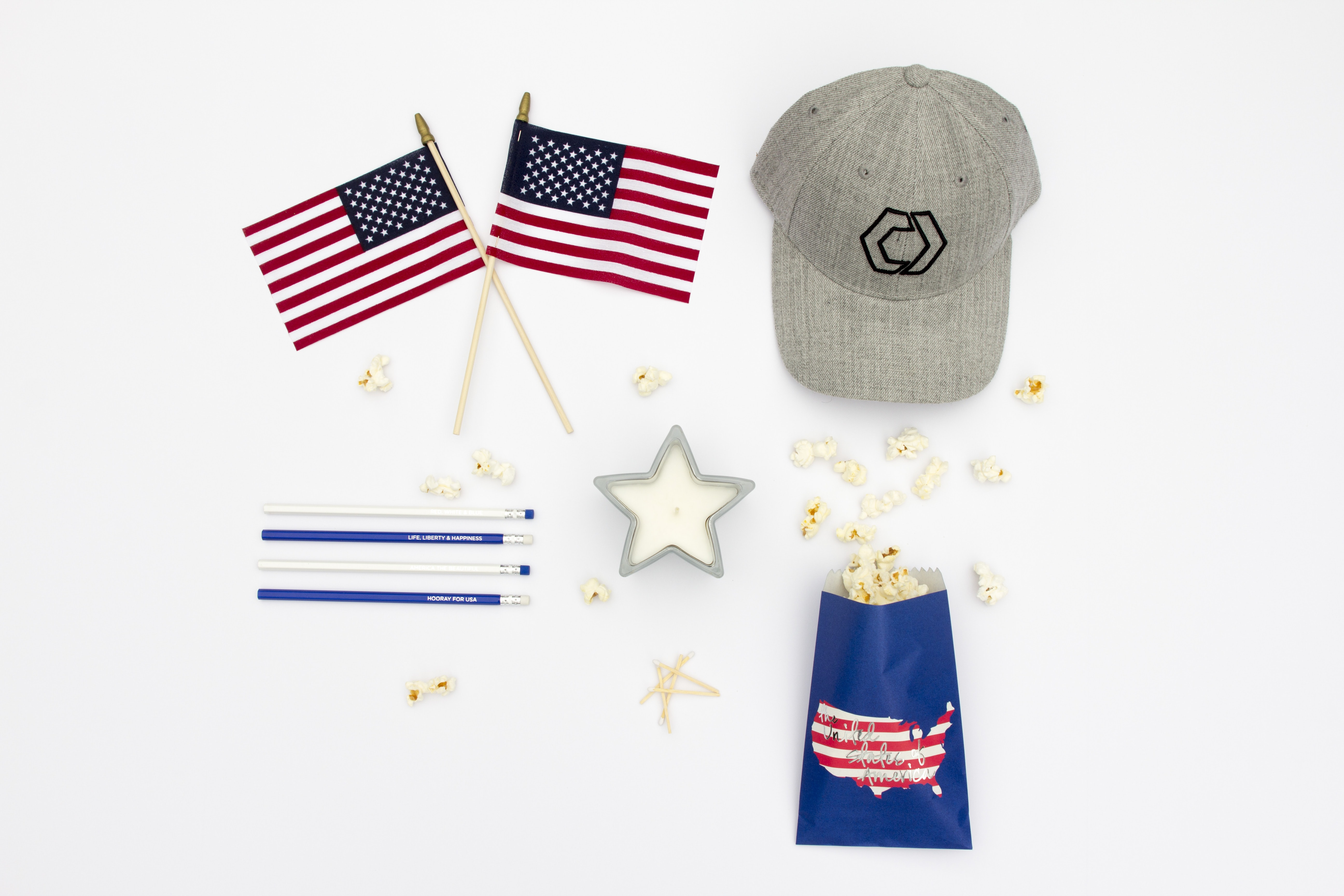Red, white, and blue Americana gear on a white surface: two small American flags, a gray baseball hat, pencils, a star candle, and popcorn