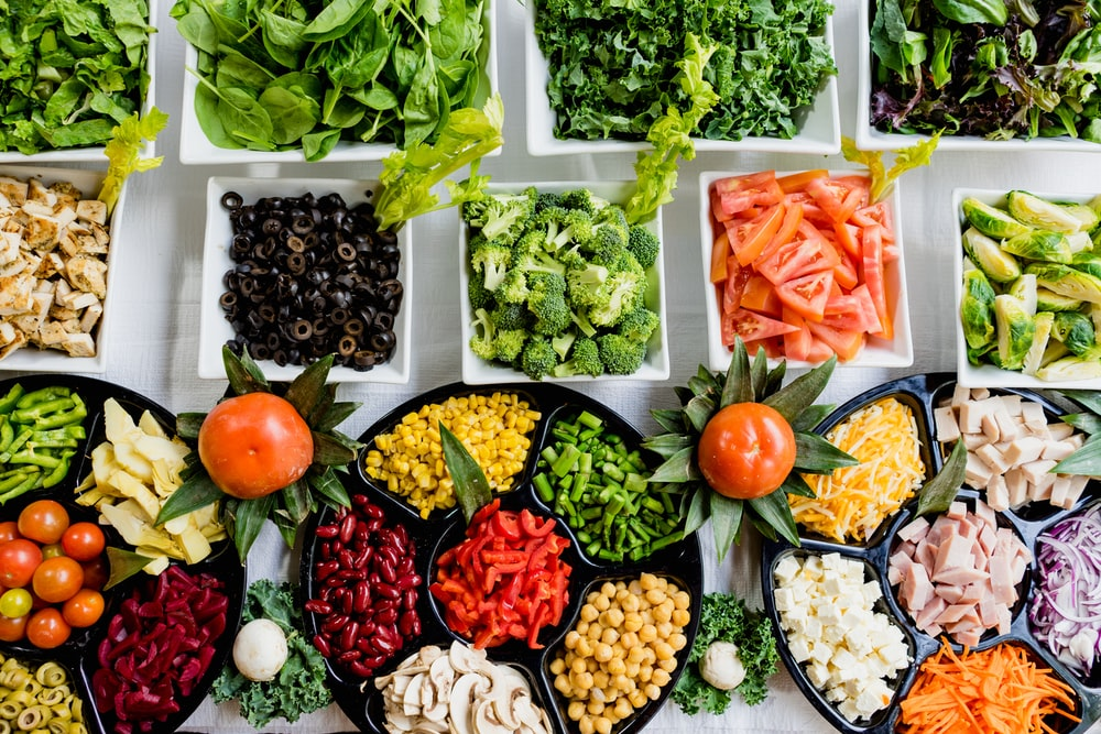 Colorful salad bar with greens, broccoli, black olives, peppers and more