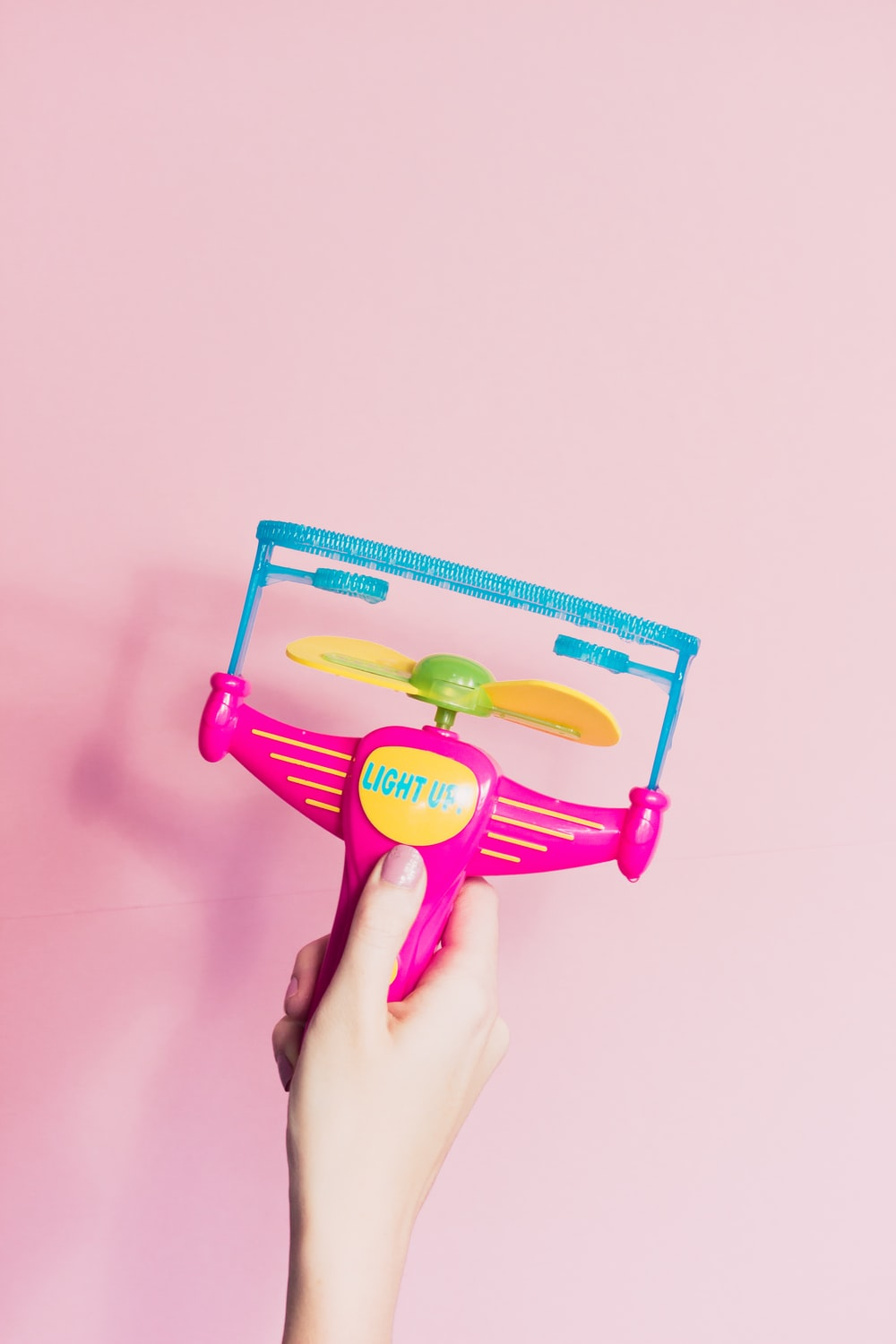 person holding pink and yellow bubble
