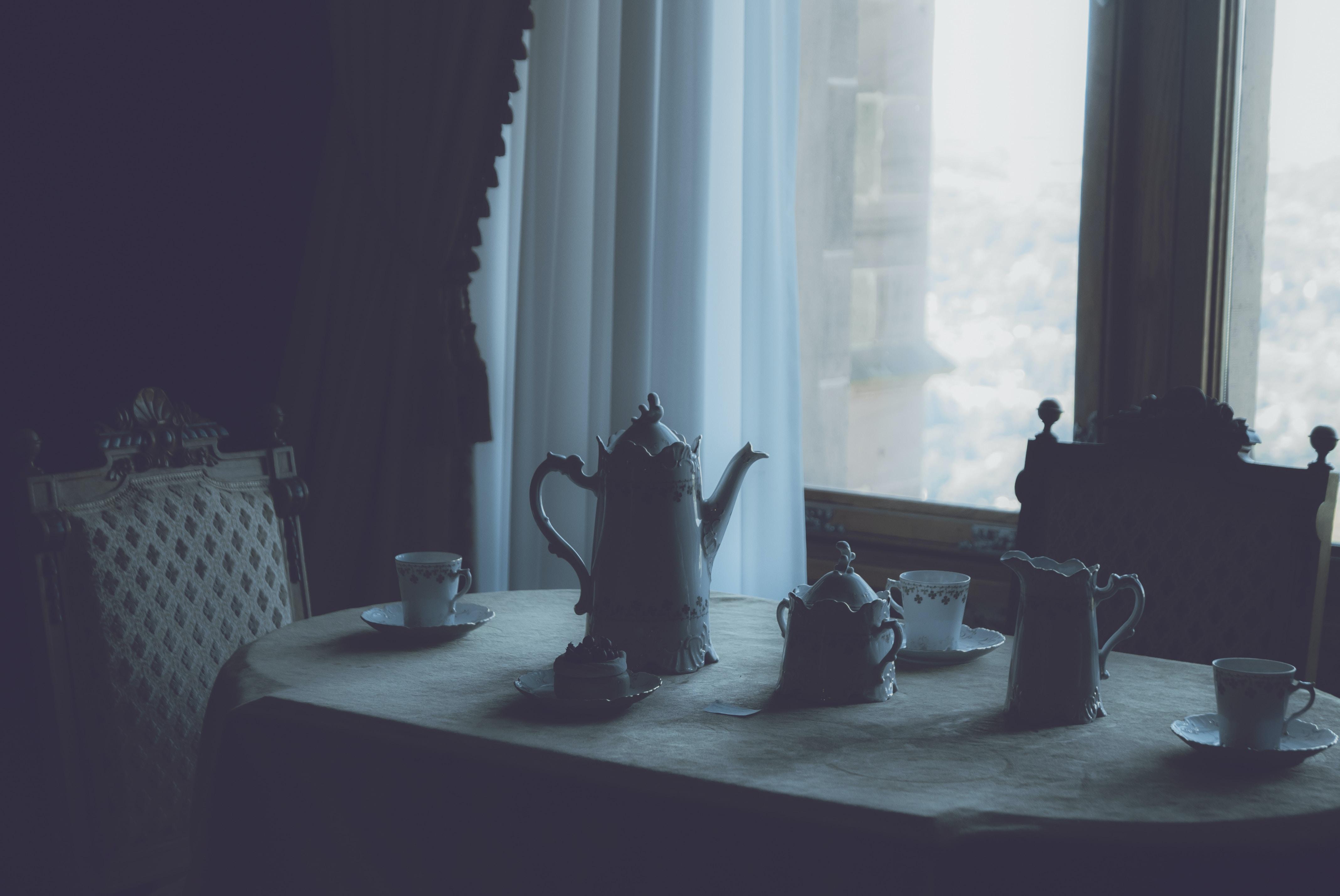 white ceramic tea set on white dining table near window