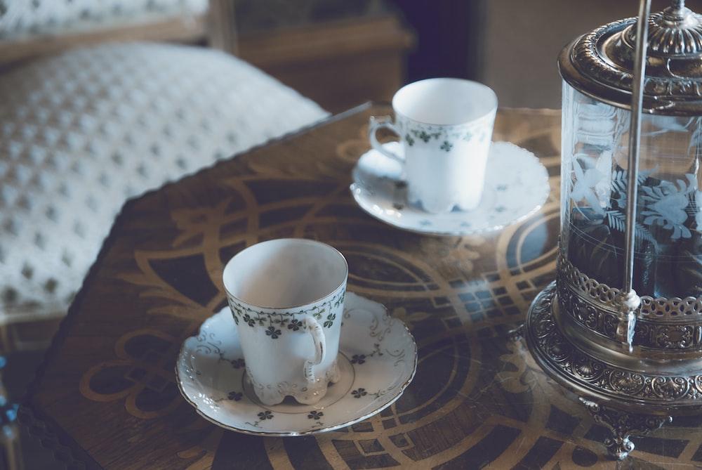 white and black floral ceramic mug on table