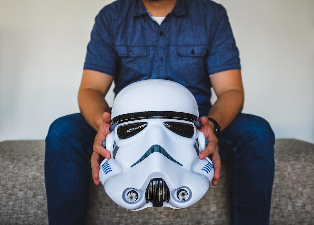 person sitting on sofa holding Stormtrooper helmet