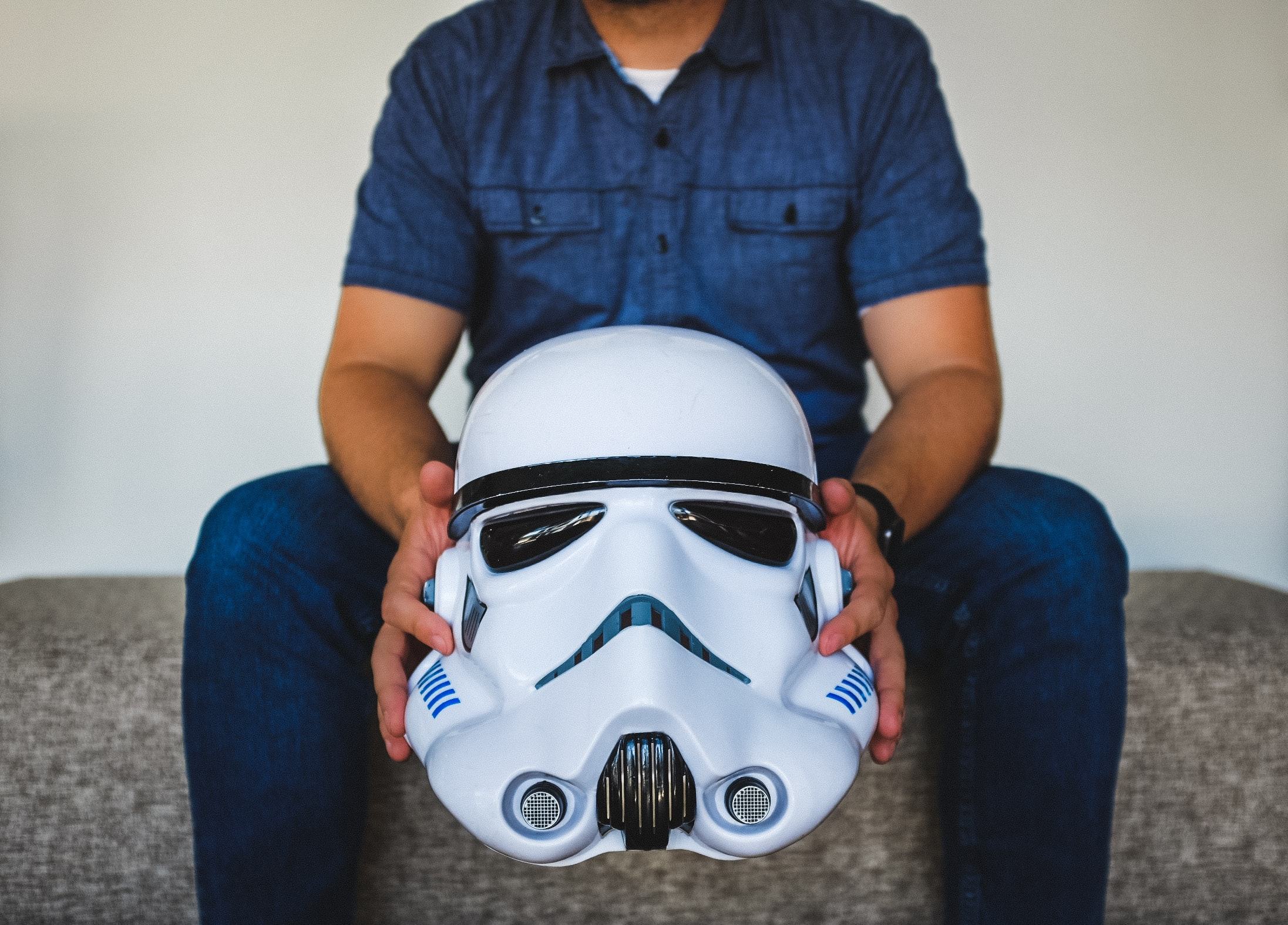 person sitting on sofa holding Stormtrooper helmet