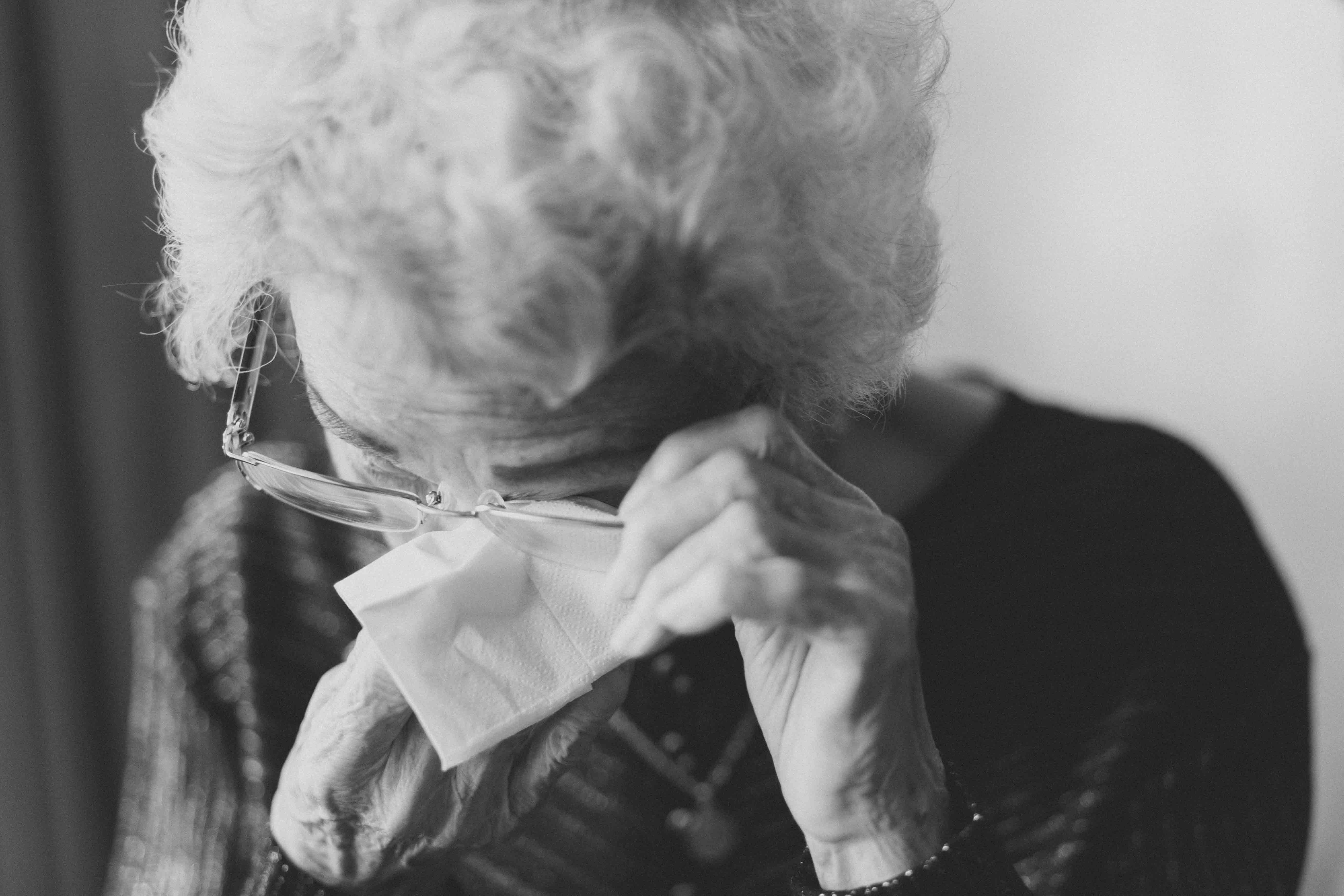 Old lady removing her spectacles to wipe her eye in black and white.