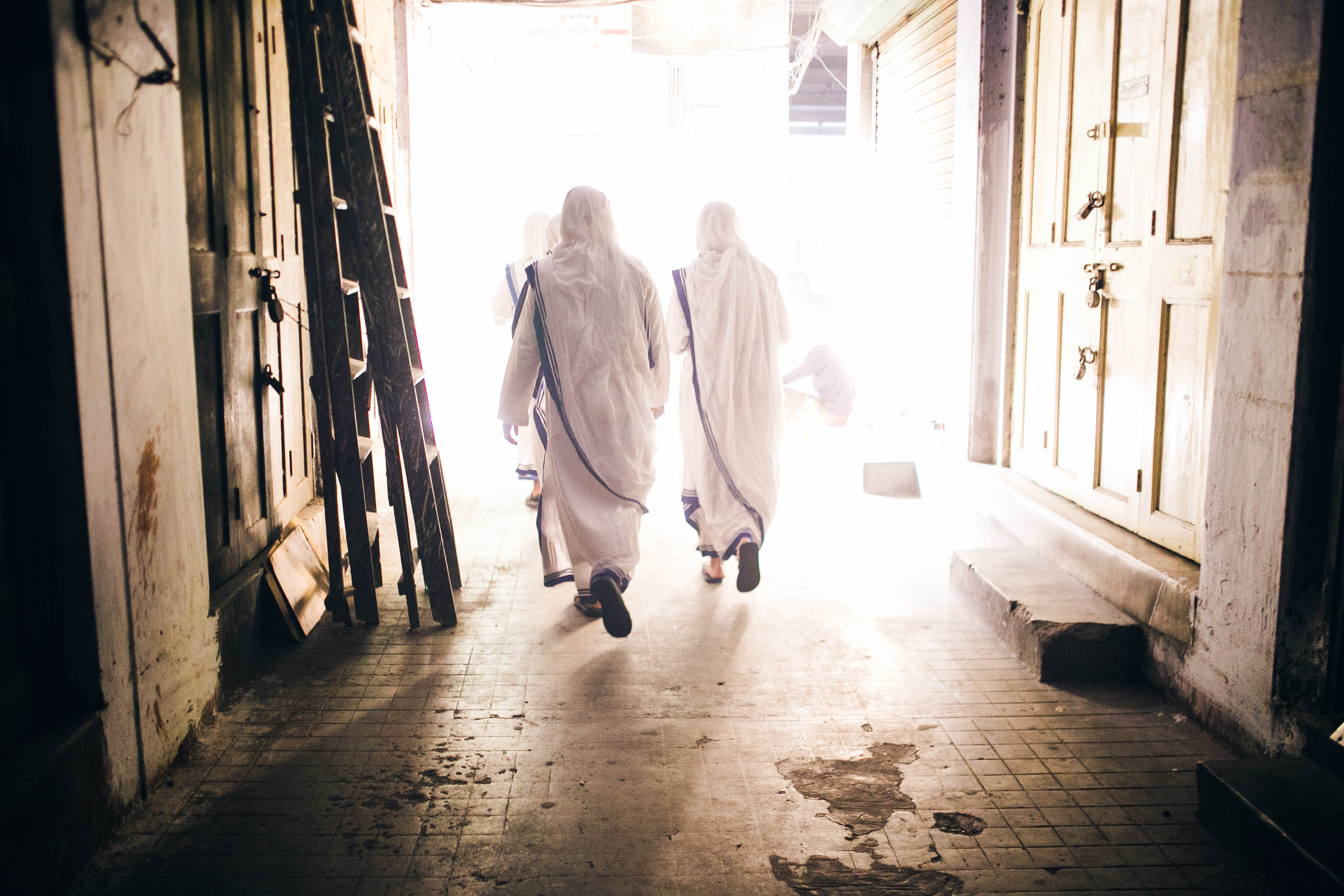 Two men dressed in white walking on a bright street.