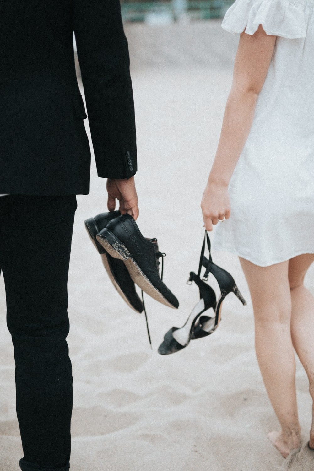 man and woman walking barefooted on white sand holding shoes and sandals