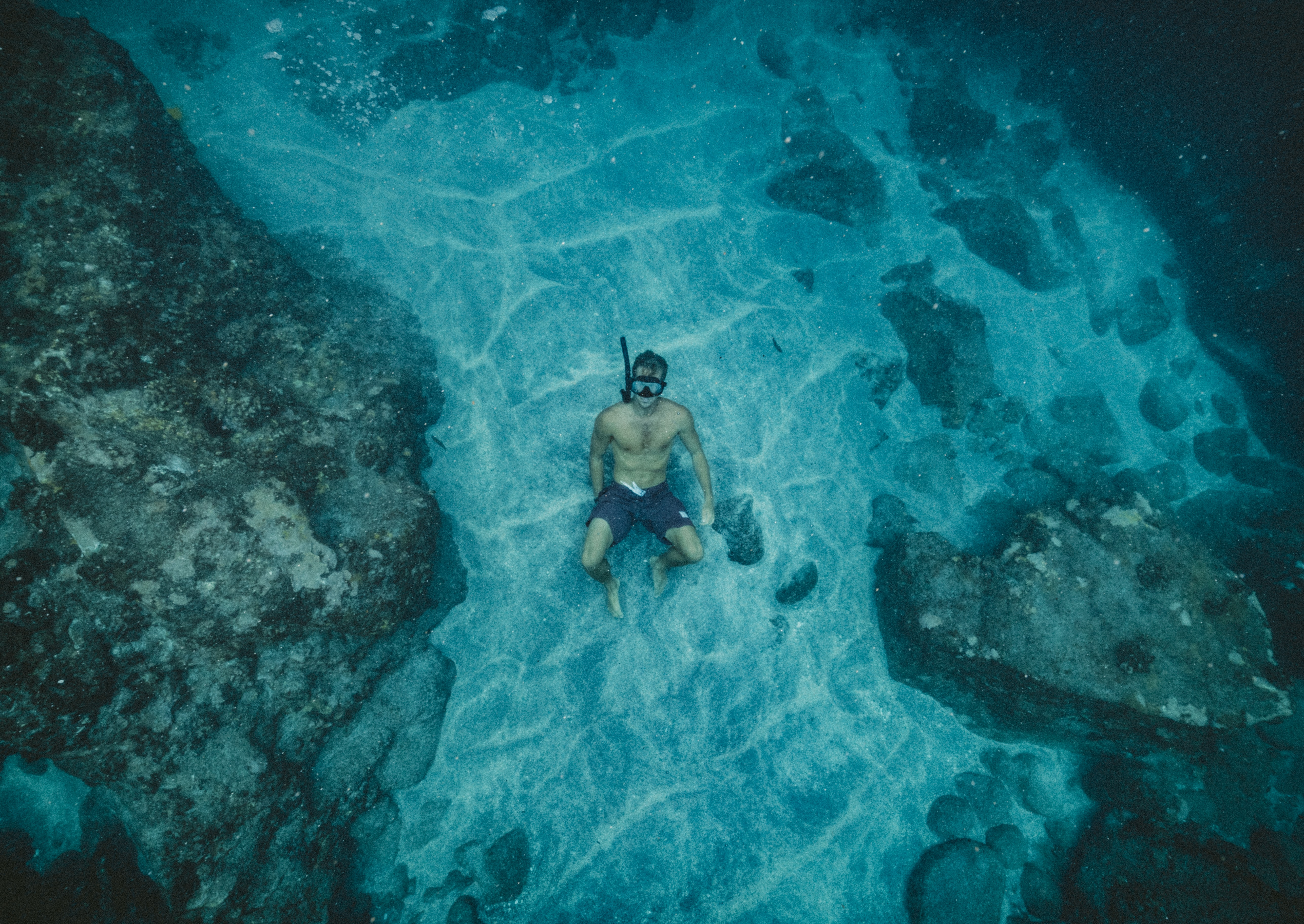 A man free diving in the sea surrounded by coral and rocks
