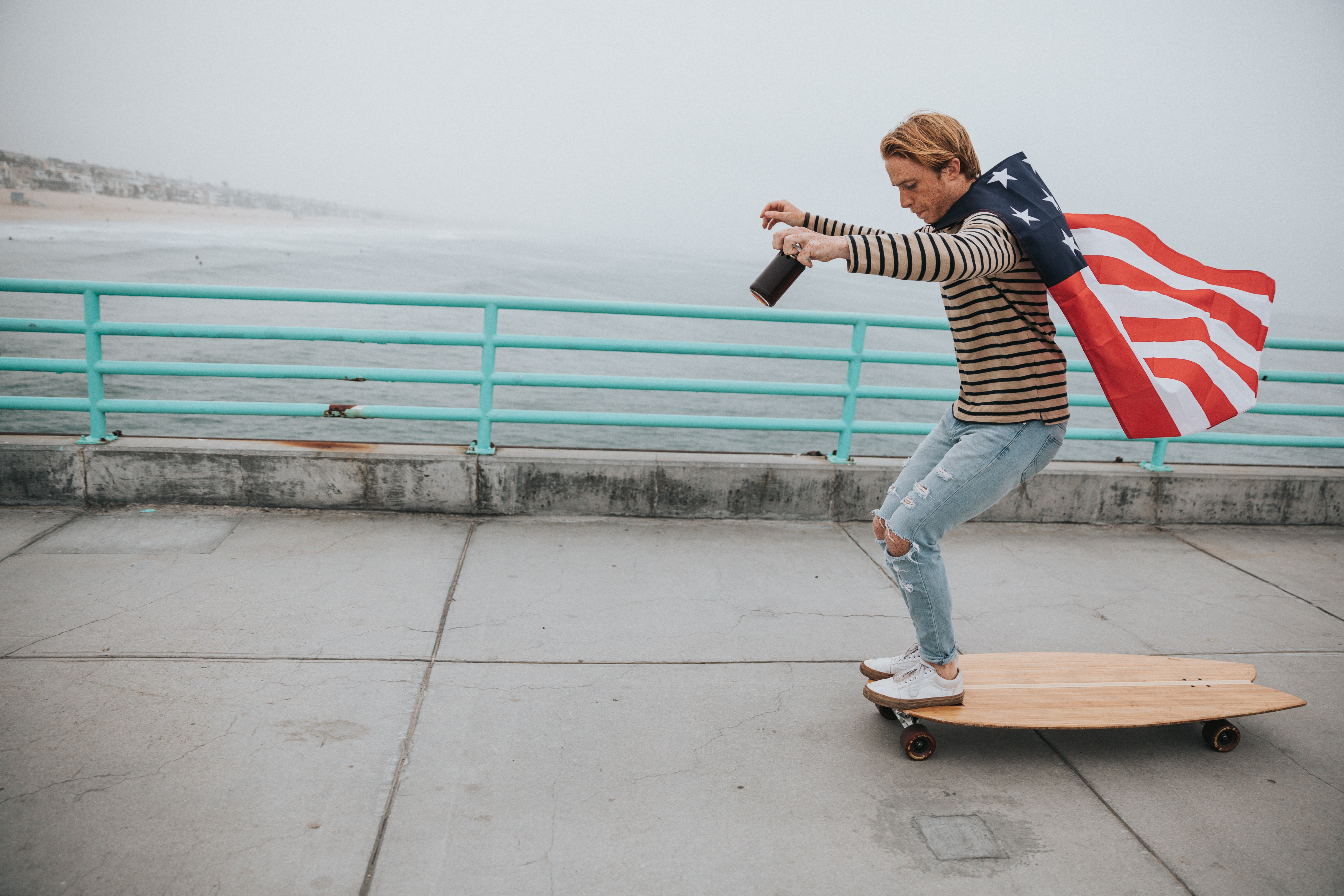 man wearing US flag cape while riding on longboard near body of water during daytime