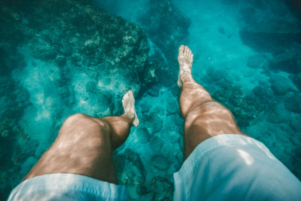 underwater photography of a person wearing white shorts